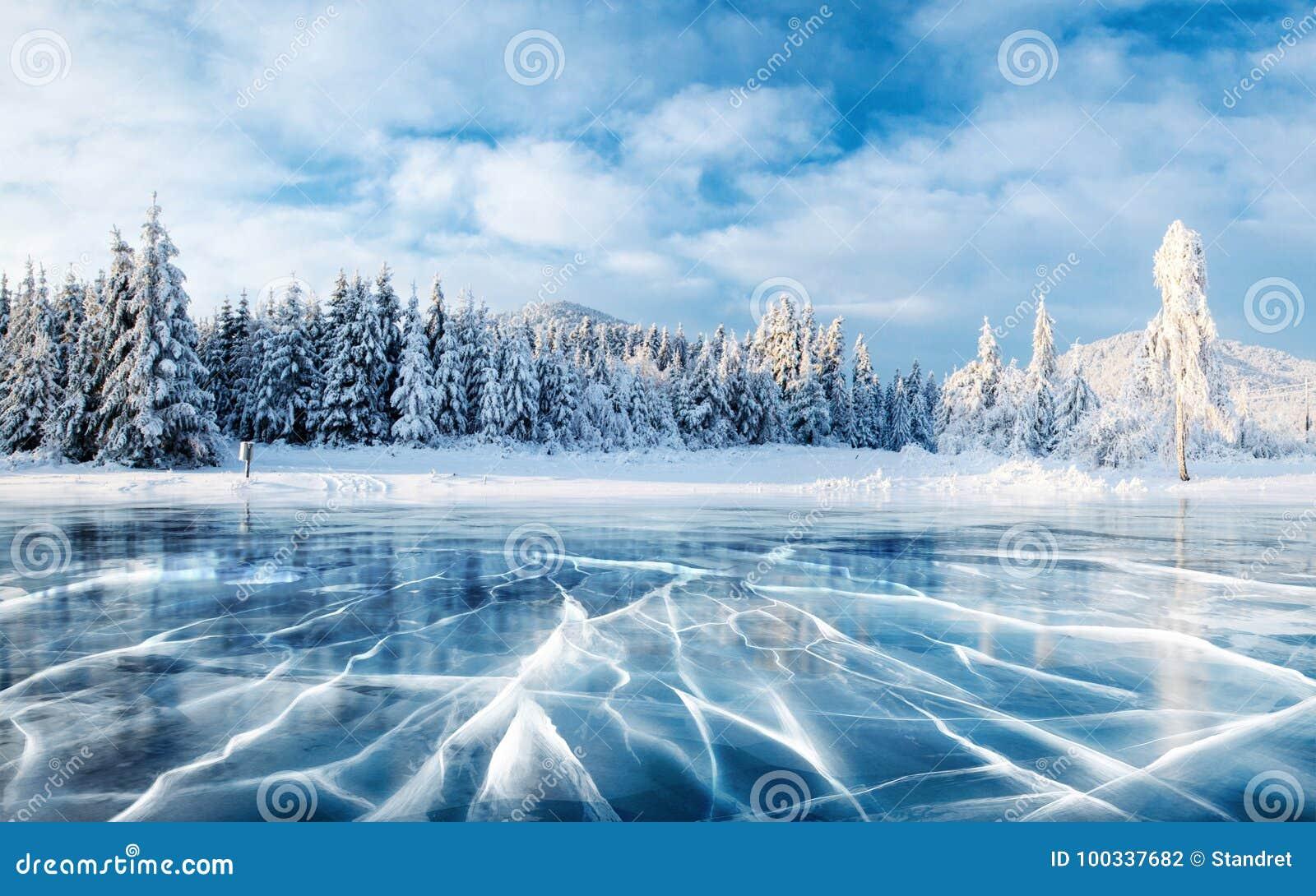 Glace et fissures bleues sur la surface de la glace Lac congelé sous un ciel bleu pendant l hiver Les collines des pins L hiver