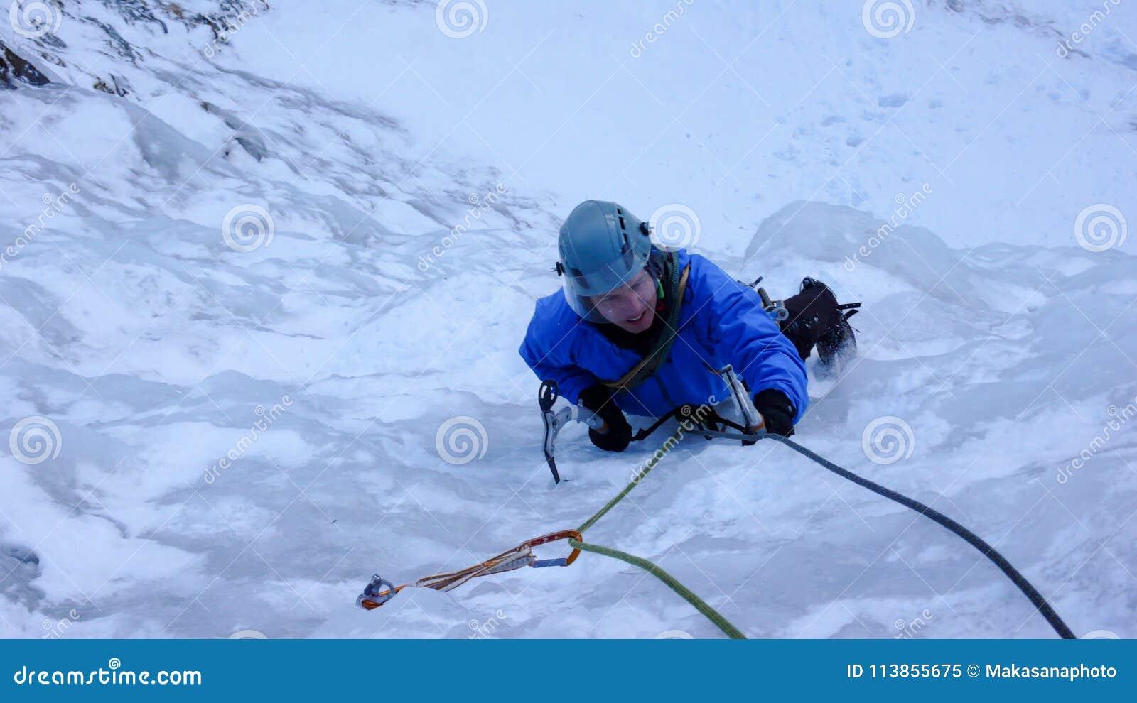 Glaciériste masculin dans une veste bleue sur une cascade congelée raide en hiver profond dans les Alpes de la Suisse