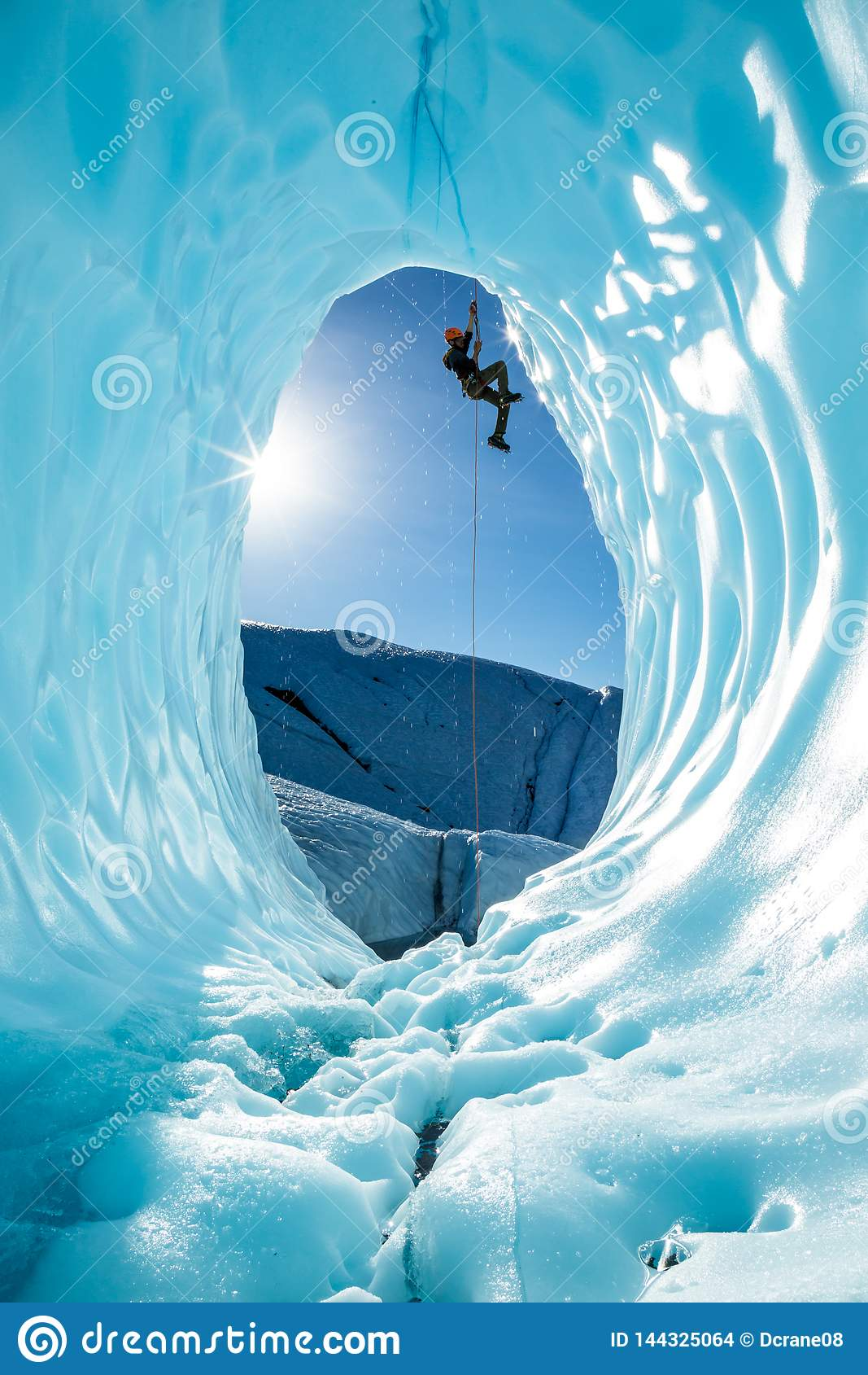 Glaciériste montant une corde au-dessus de l entrée de la grande caverne de glace bleue sur le glacier de Matanuska en Alaska