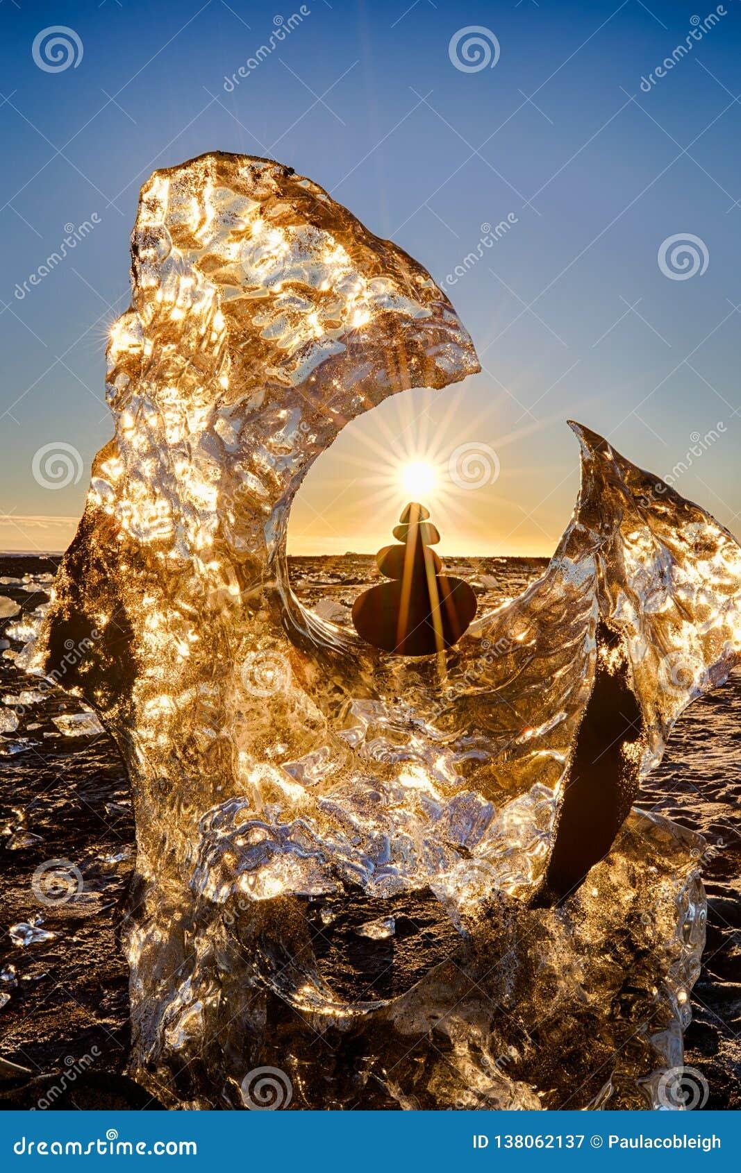 Glacier et roches équilibrées avec l étoile du soleil sur Diamond Beach de l Islande avec le sable noir