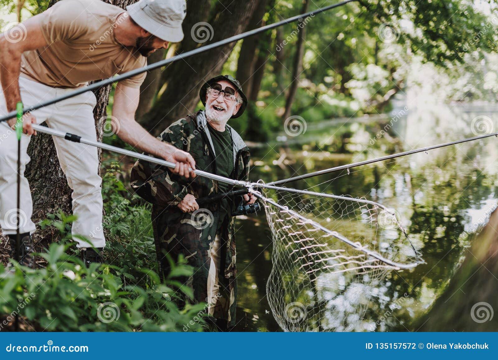 Glad äldre fiskare som tycker om helg med hans son