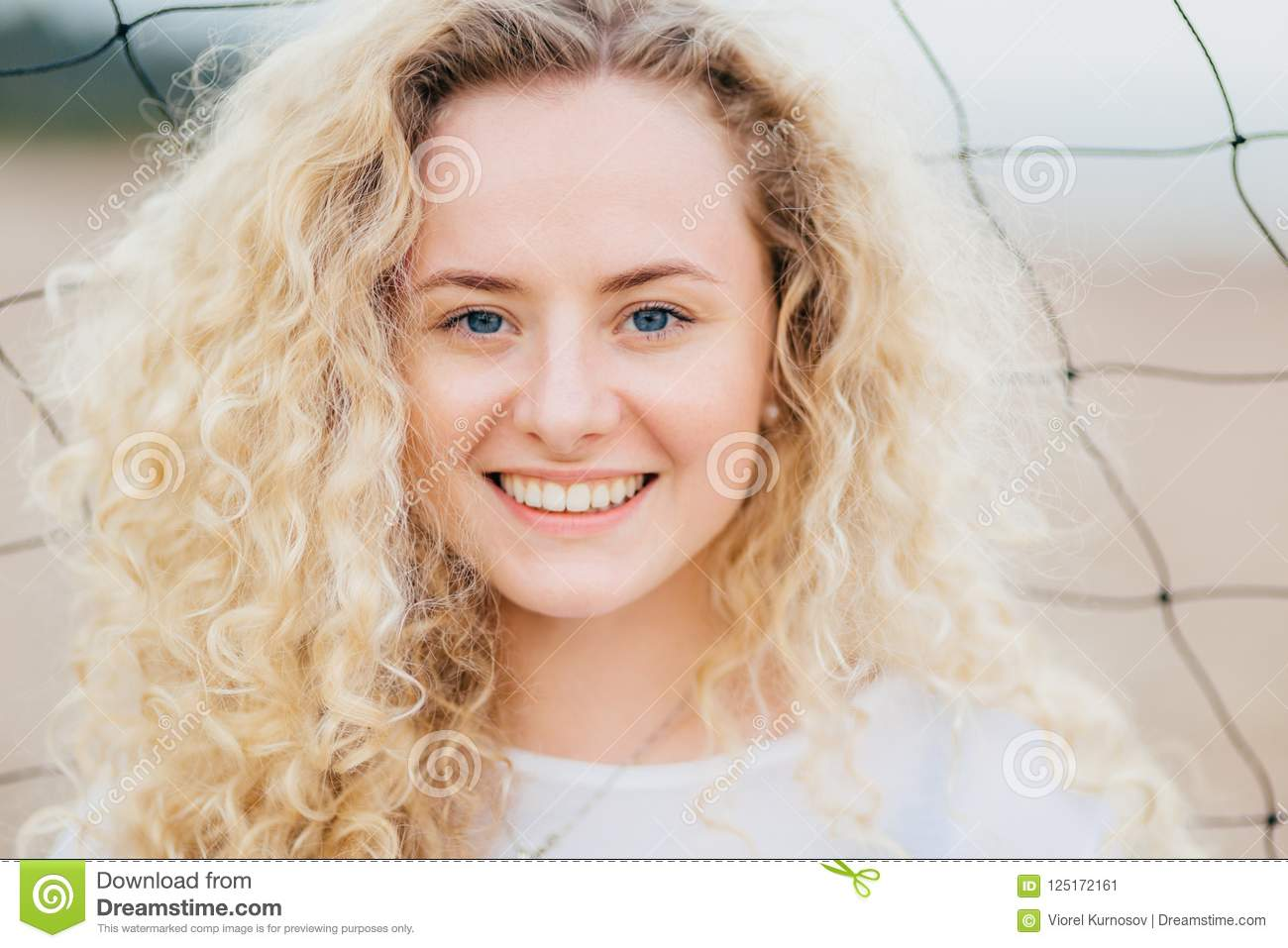 Glad Curly Caucasian Woman With Toothy Smile Has Curly Bushy Light