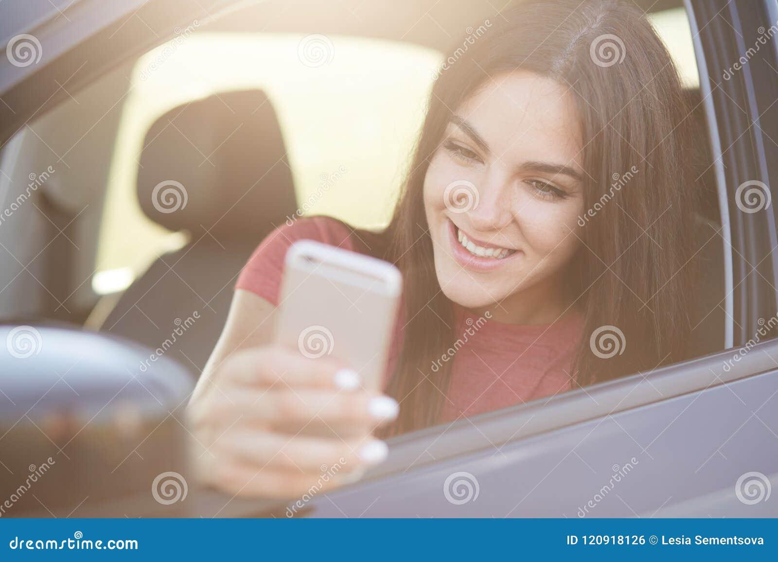 Glad European-het wijfje met lang donker haar, gelukkig om bericht op slimme die telefoon te ontvangen, stelt in auto, ophoudt op