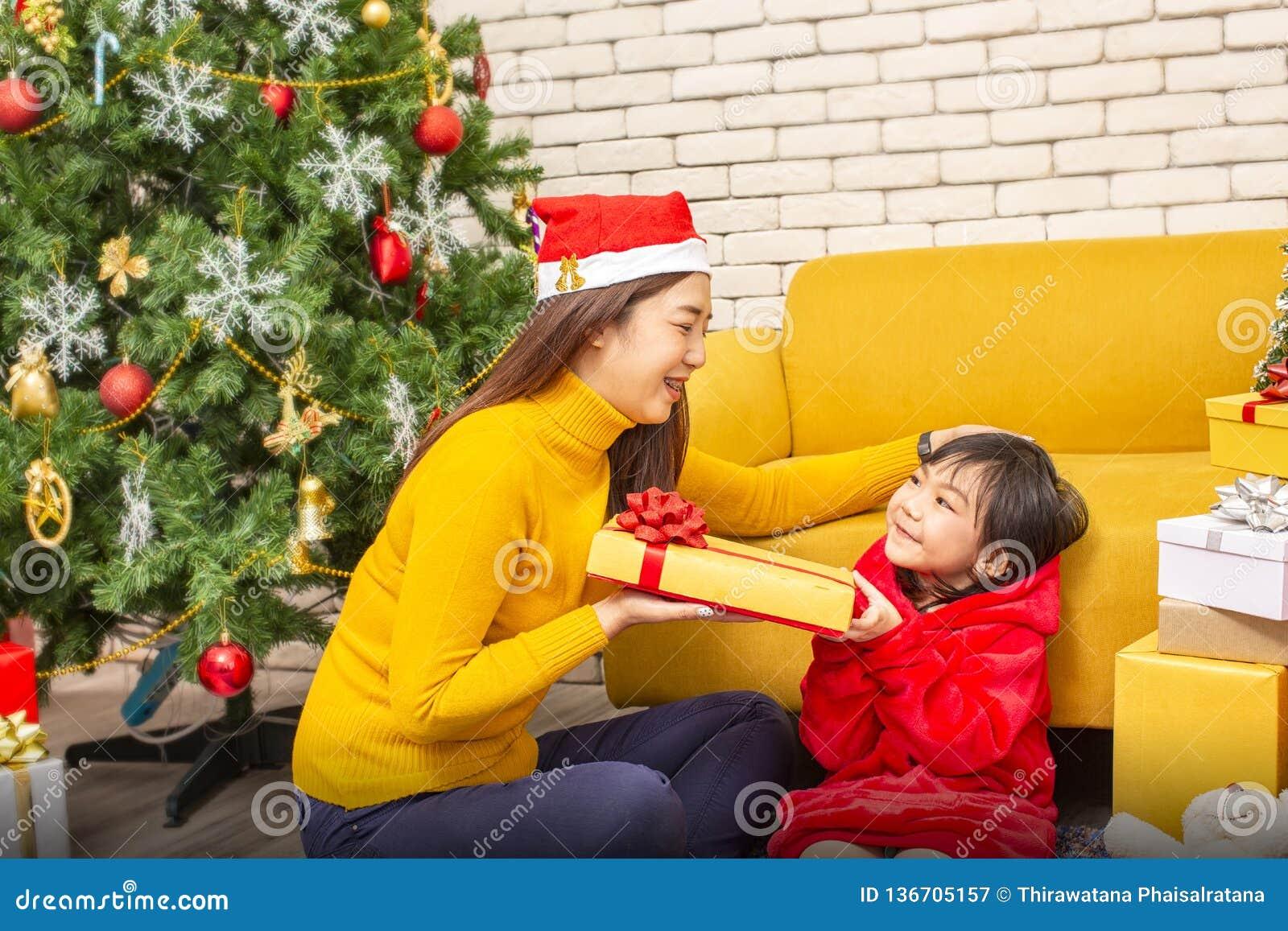 Glad jul och lyckligt lycklig nytt år för ferier eller Mamman ger gåvor till barn Den gulliga flickan ger hans älskade moder en g