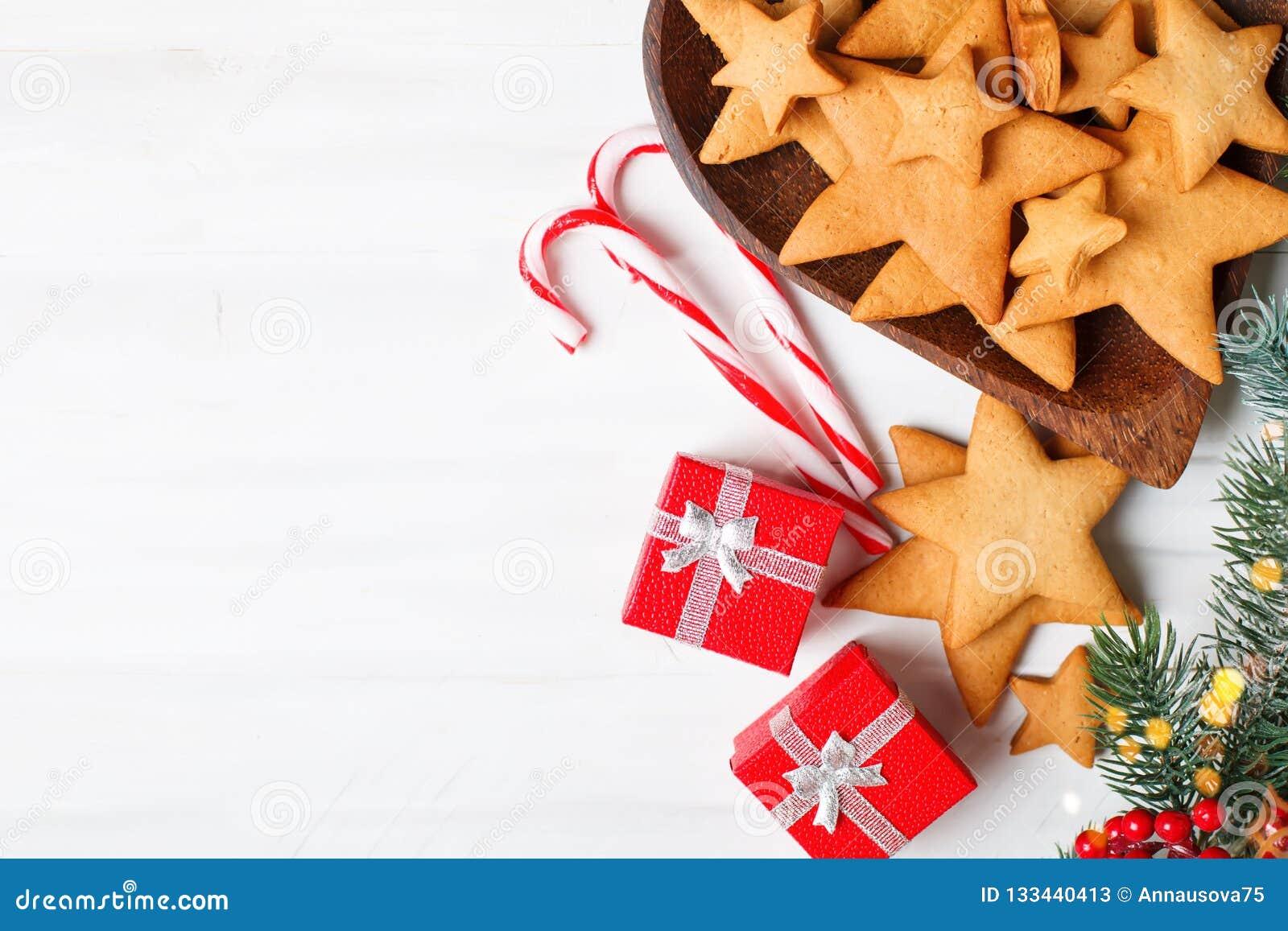 Glad jul och lyckligt nytt år Kakor, gåvor och gran-träd filialer på en vit trätabell Selektivt fokusera