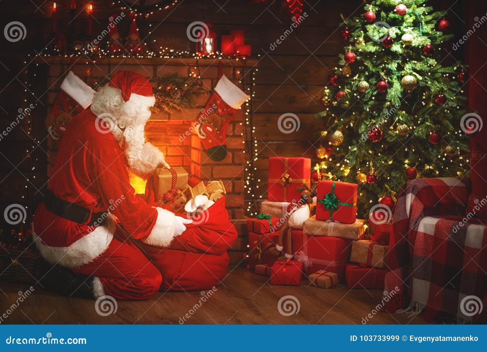 Glad jul! Santa Claus nära spisen och trädet med gi