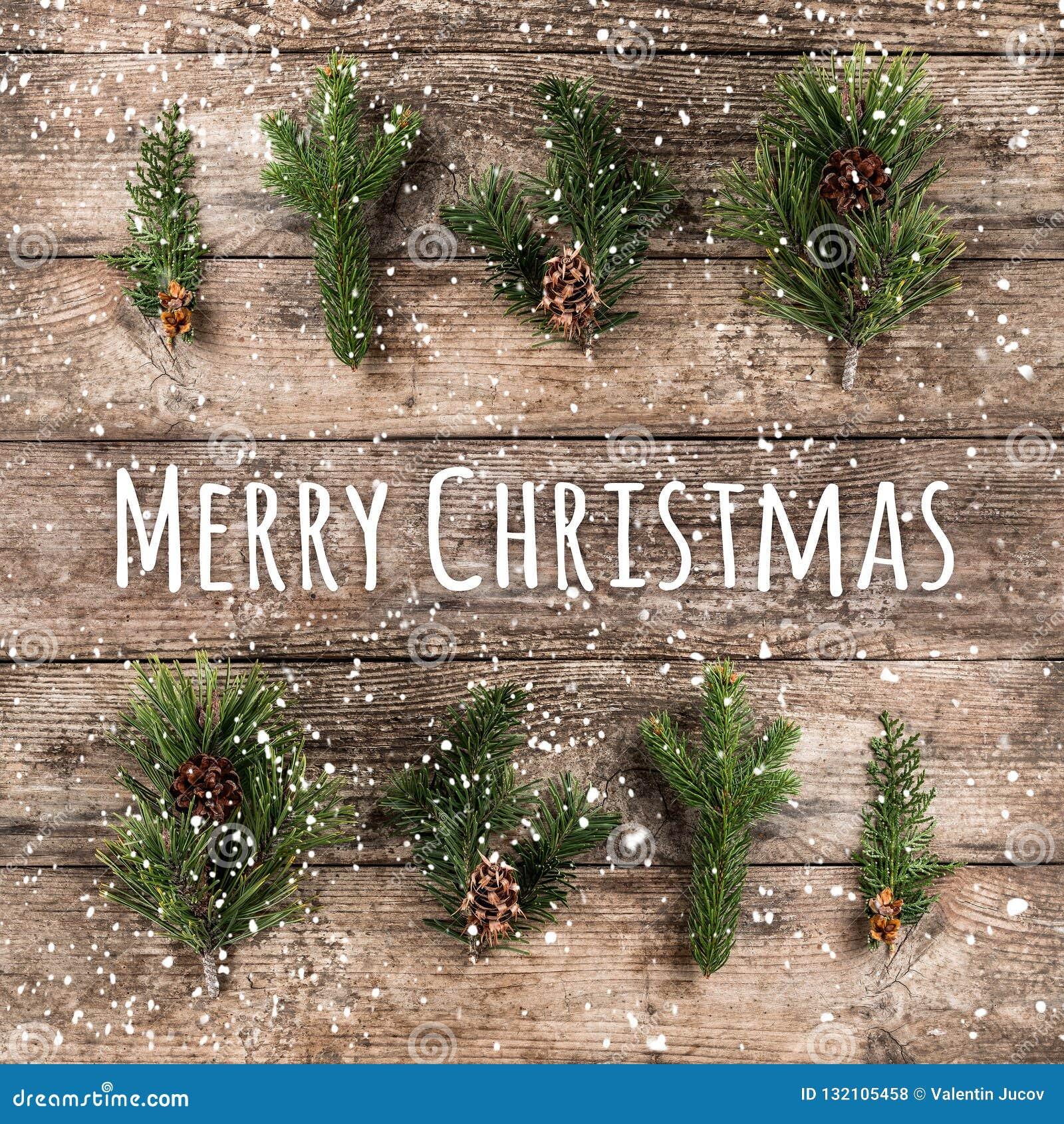 Glad jul som är typografisk på träbakgrund med granfilialer, sörjer kottar och snöflingor på träbakgrund Xmas och nytt
