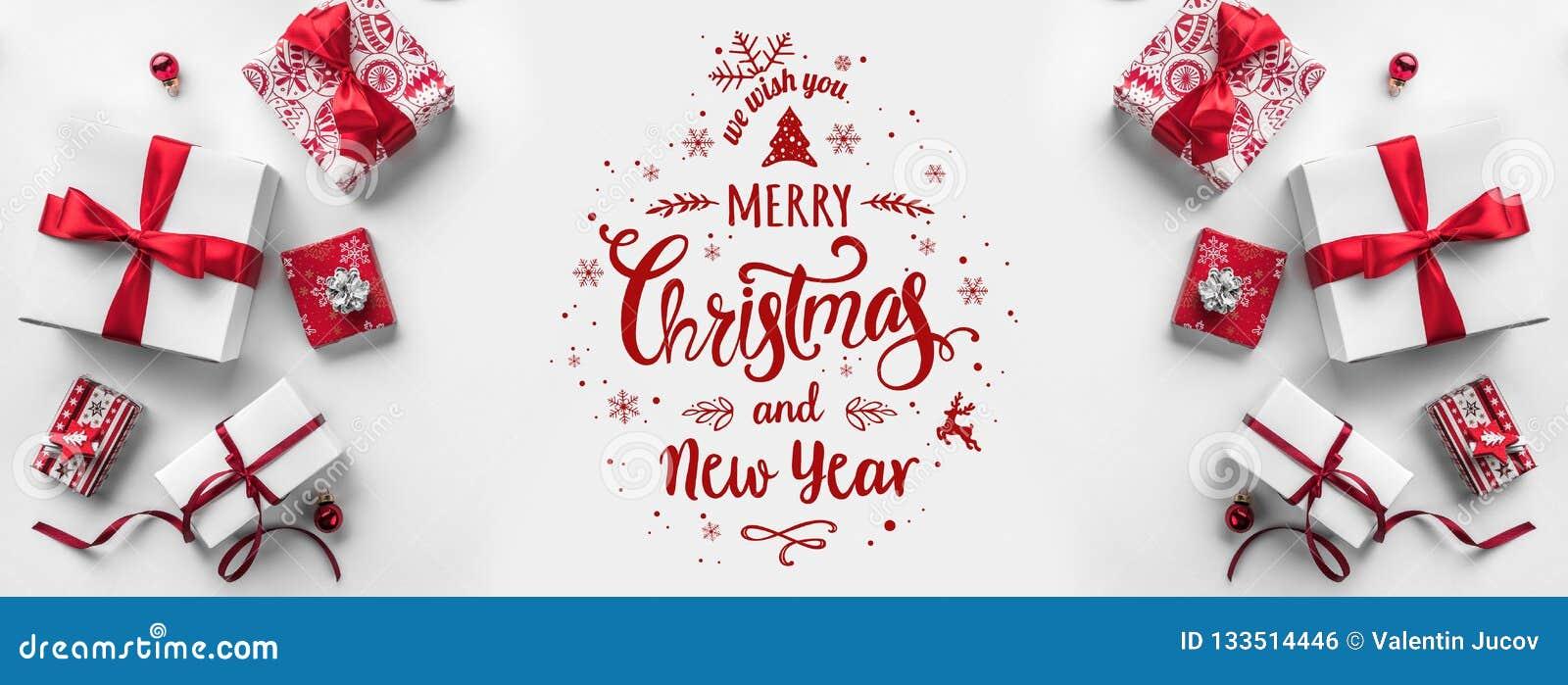 Glad jul som är typografisk på vit bakgrund med gåvaaskar och röd garnering