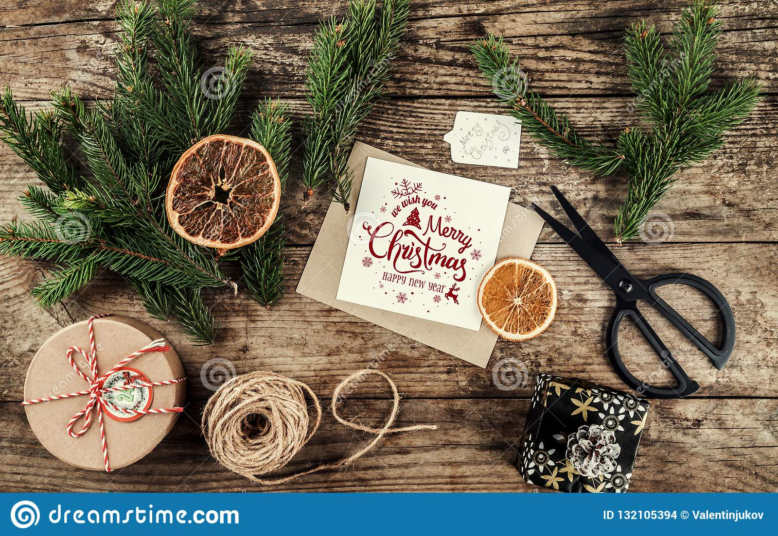 Glad julkort med granfilialer, gåvor på träbakgrund med sax och skeinen av jute Tema för Xmas och för lyckligt nytt år,
