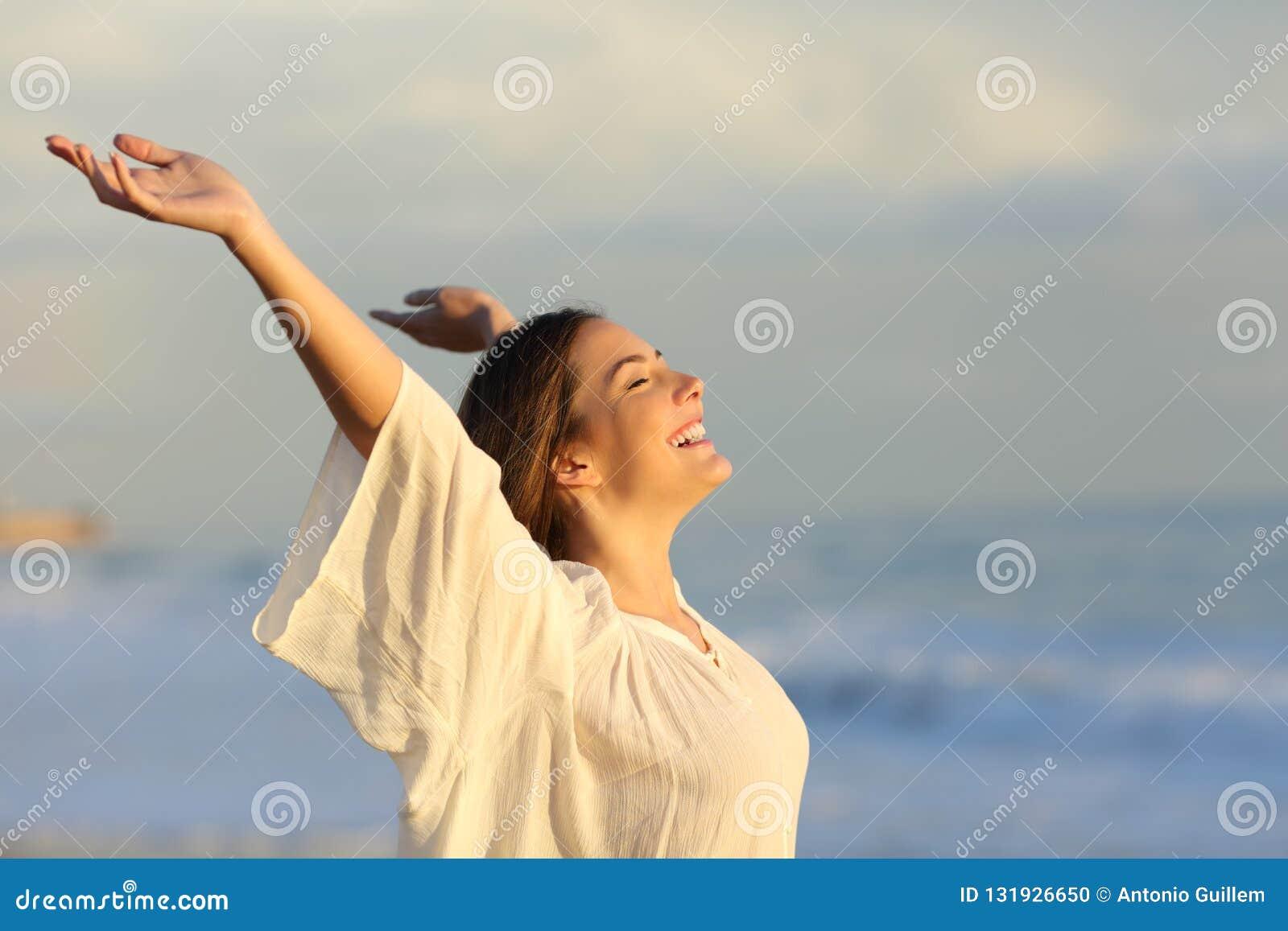 Glad kvinna som tycker om en dag på stranden