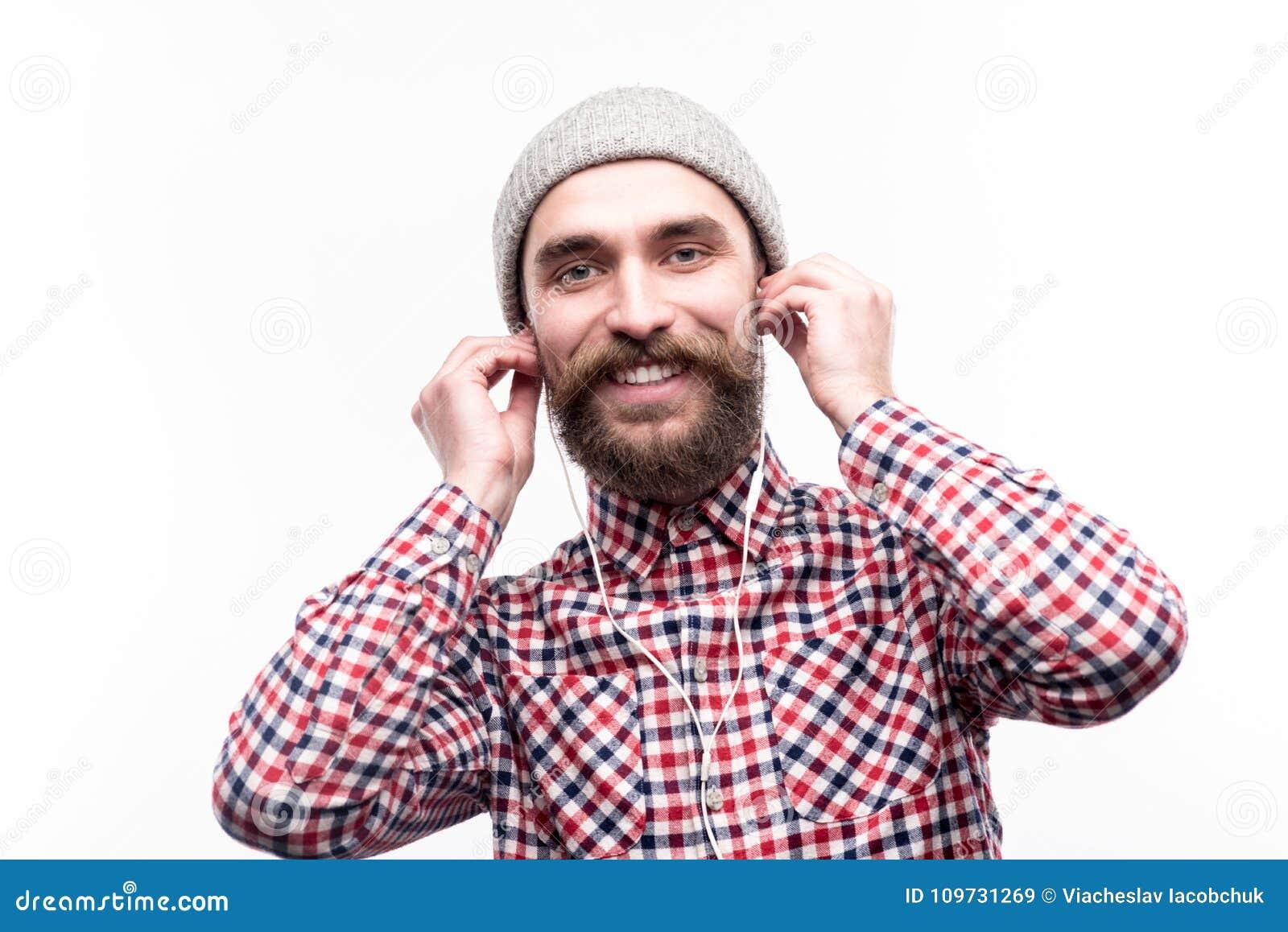 Glad man som sätter hörlurar in i hans öron