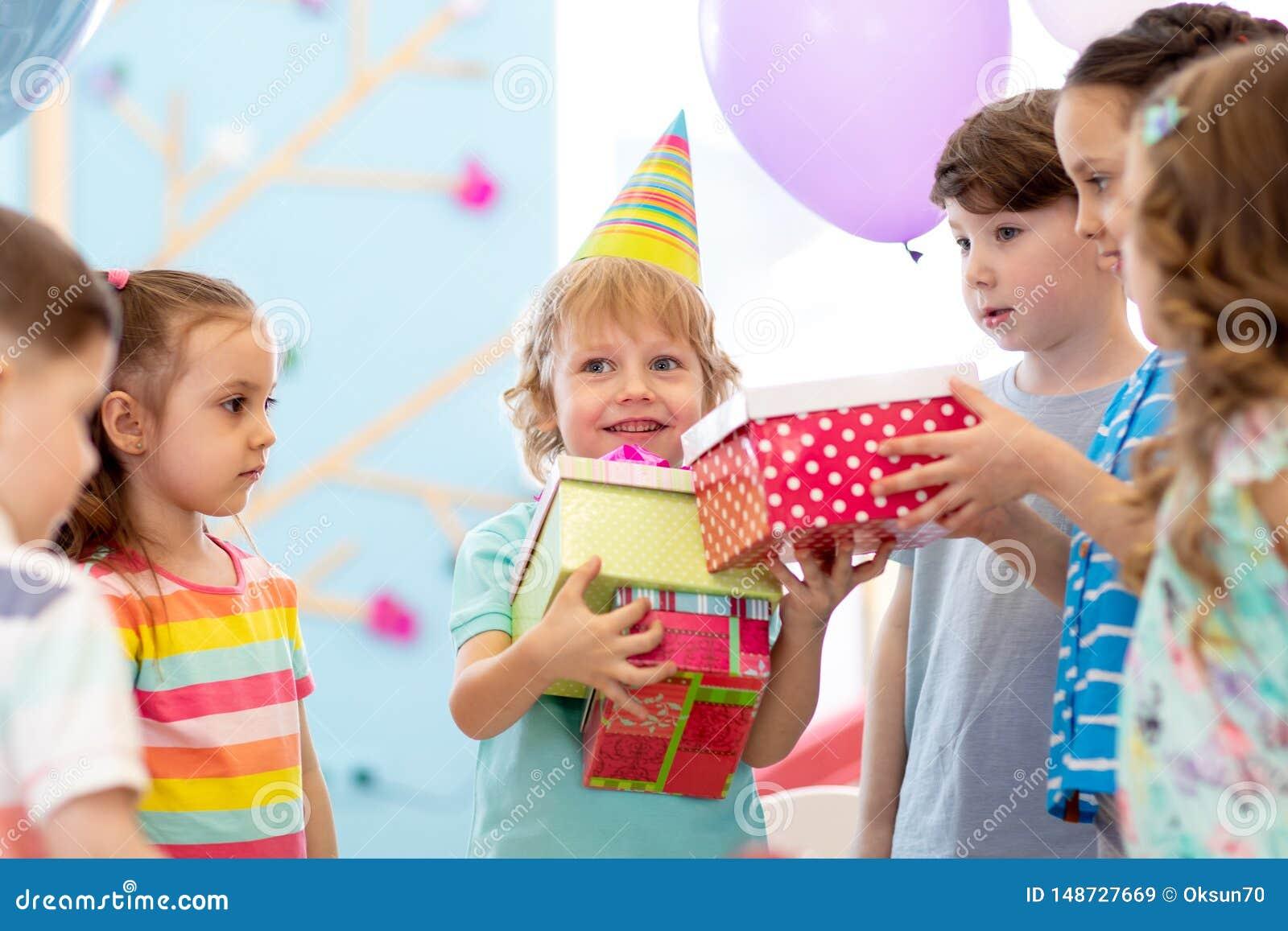 Glad pojke f?r liten unge som mottar g?vor p? f?delsedagpartiet Ferier f?delsedagbegrepp