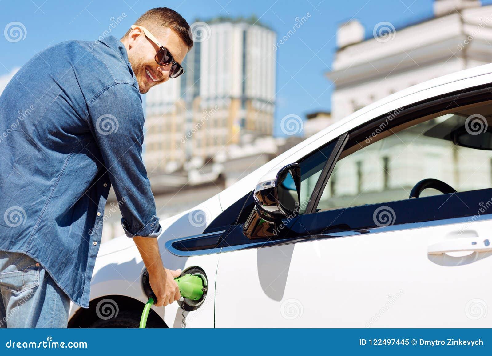 Glad stilig man som rymmer en bränsledysa