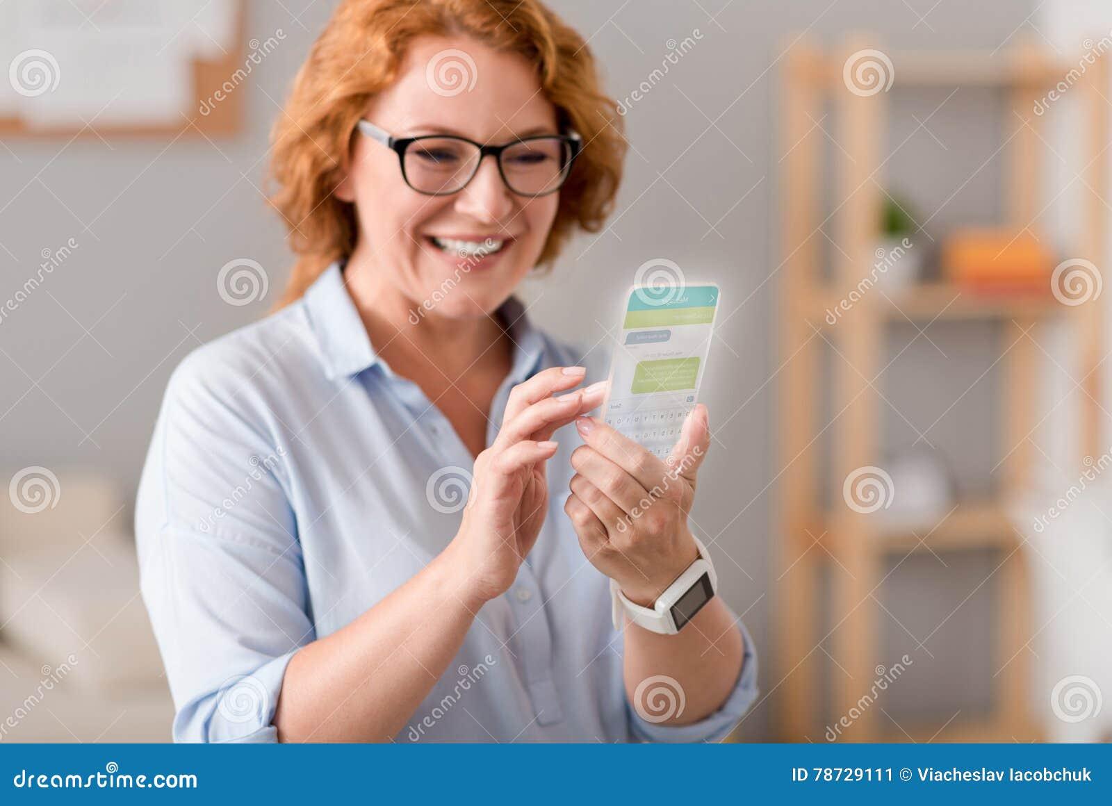 Glad vuxen kvinna som använder mobiltelefonen