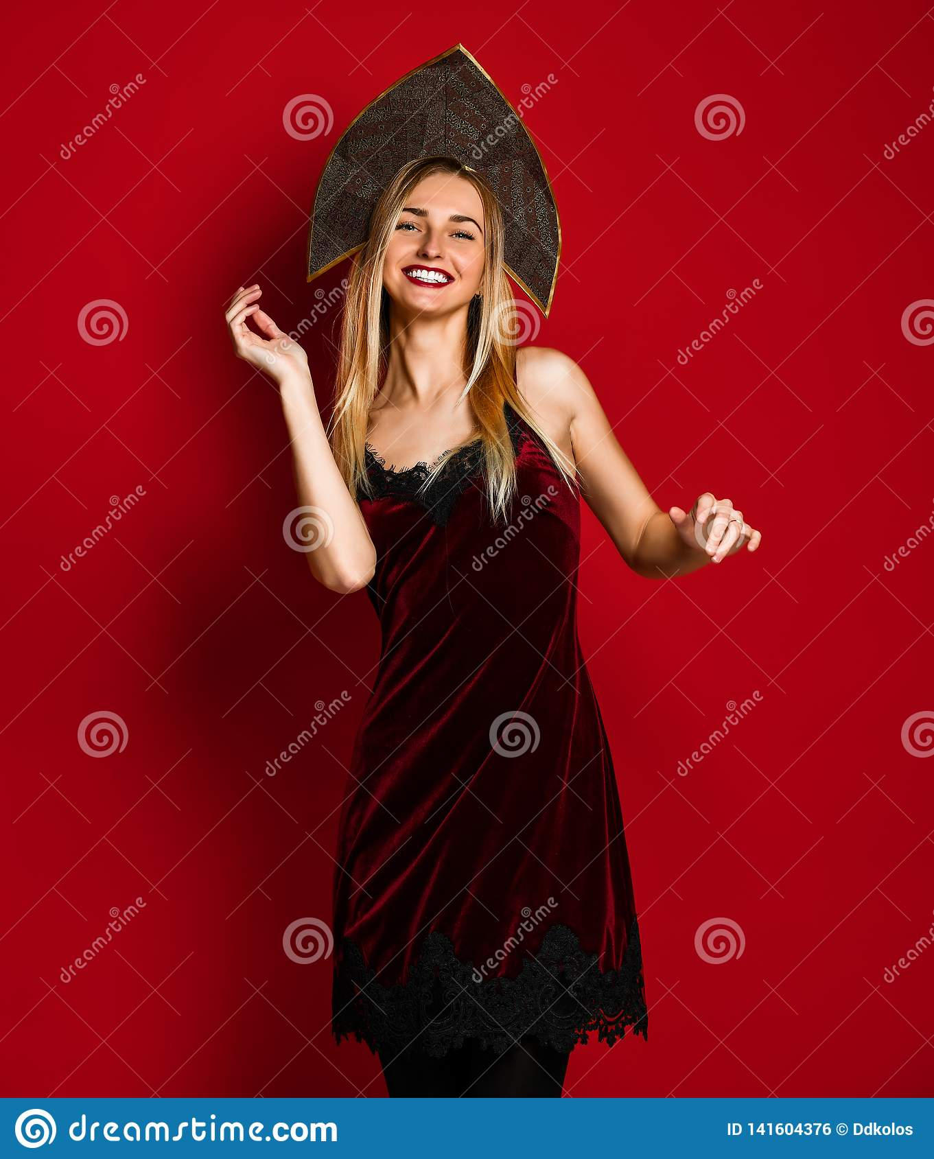 Glad woman in red dress happy dancing and relaxing , celebrating . Indoor photo of pretty lady in kokoshnik hat having fun