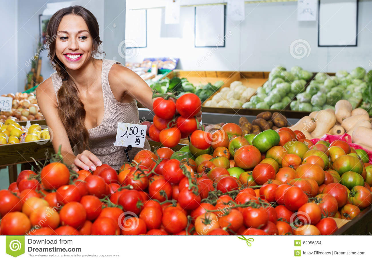 Glad young woman picking fresh tomatoes