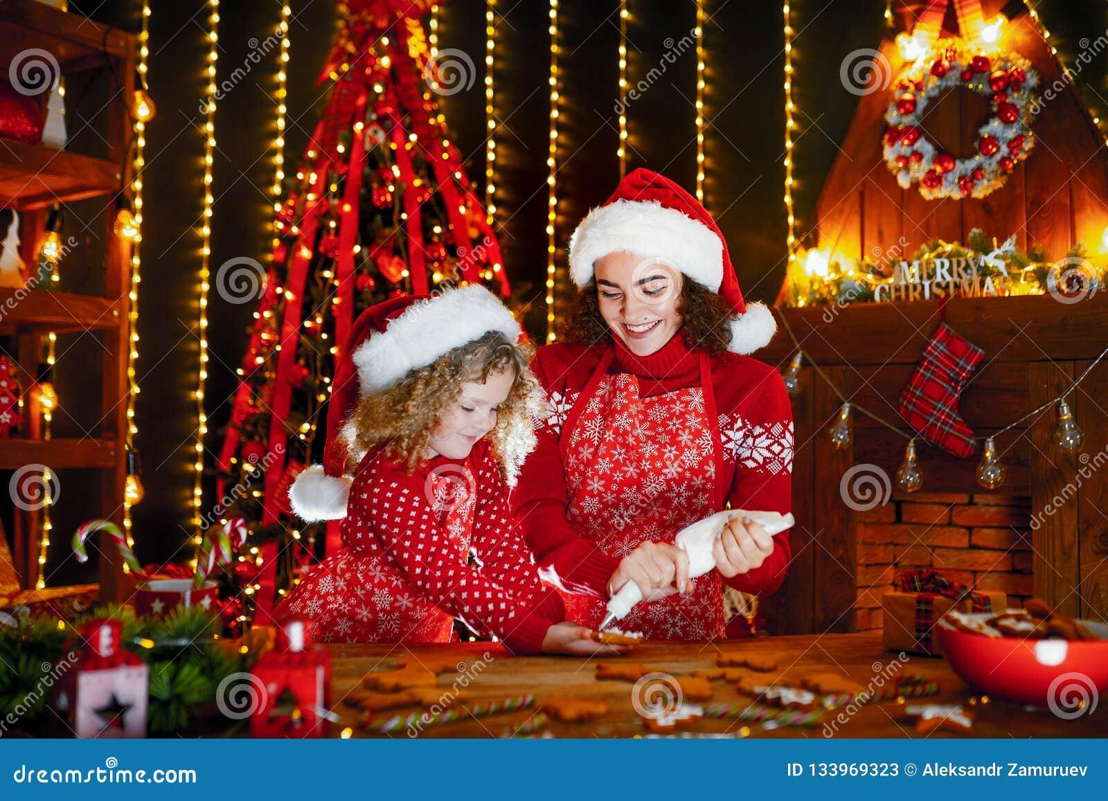 Glada lyckliga ferier för jul Gladlynt gullig lockig liten flicka och hennes äldre syster, i att laga mat för santas hattar