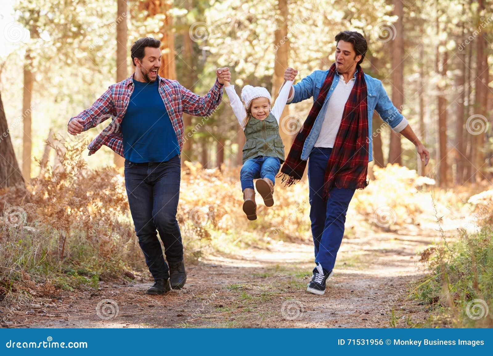 Glade manliga par med dottern som går till och med nedgångskogsmark