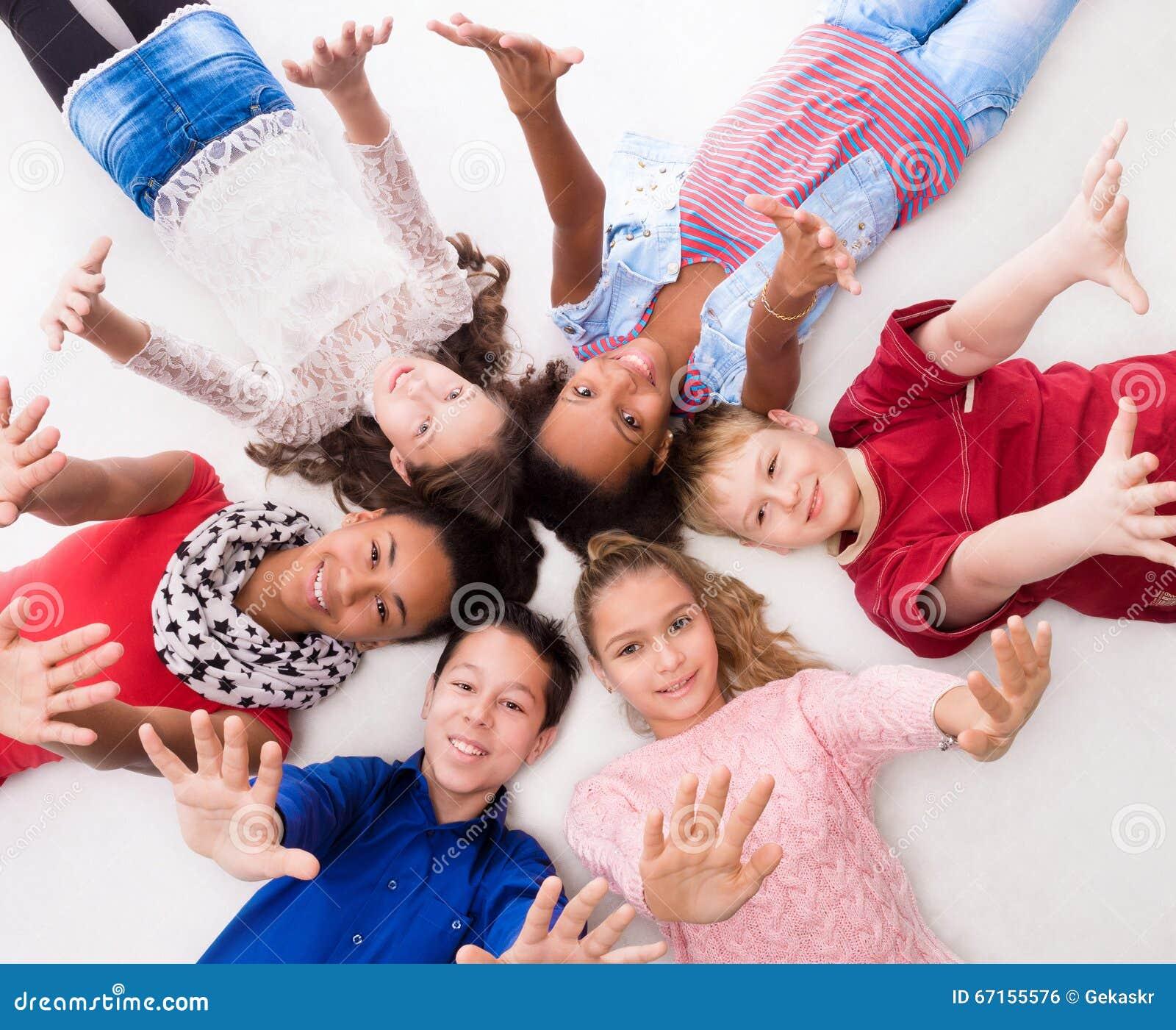 Glade tonåringar som ligger på golvhuvudet - - huvud