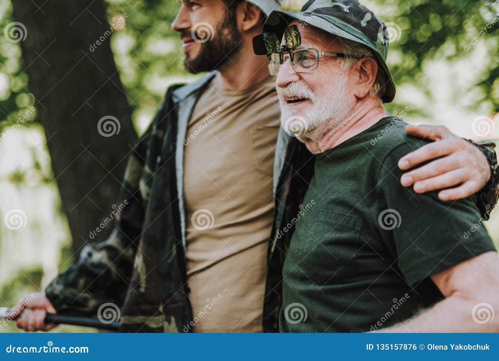 Gladlynt äldre man som vilar med hans vuxna son