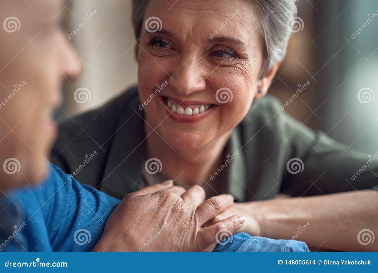 Gladlynt åldrig dam som ser med förälskelse till mannen