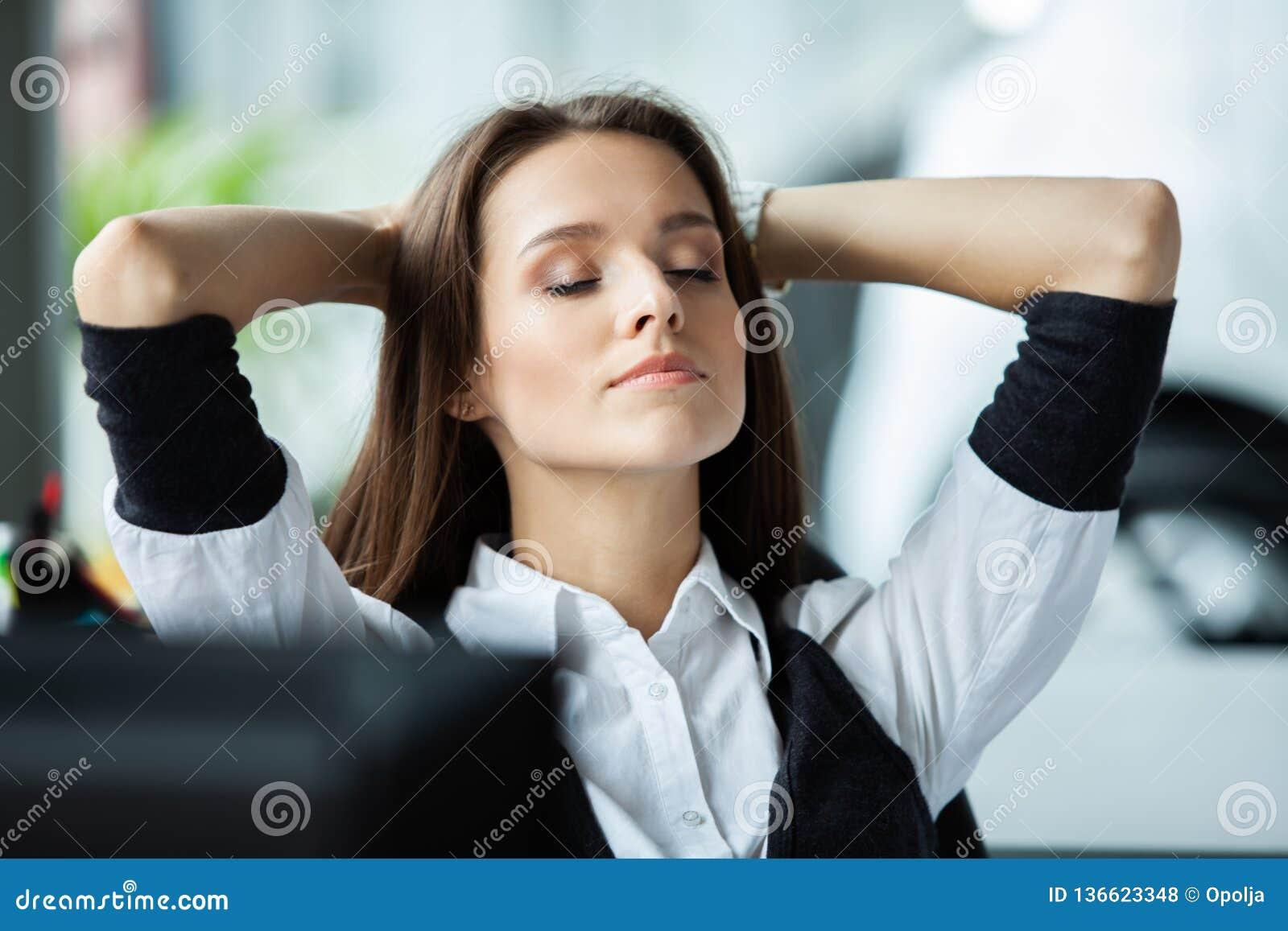 Gladlynt affärskvinna som drömmer på arbetsplatsen Kvinnliga tagande för kontorsarbetare bryter efter det gjorda jobbet Affärsdam
