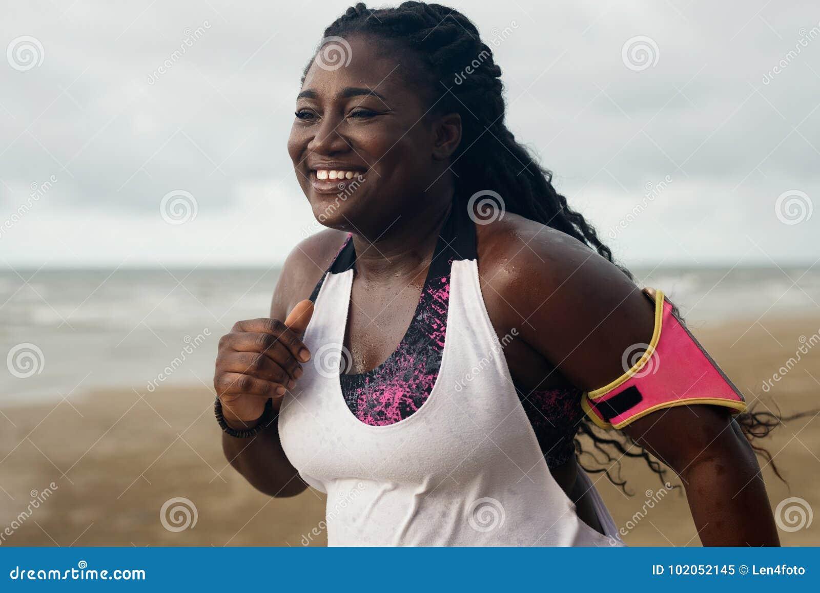 Gladlynt afrikansk löpare som joggar under utomhus- genomkörare på stranden