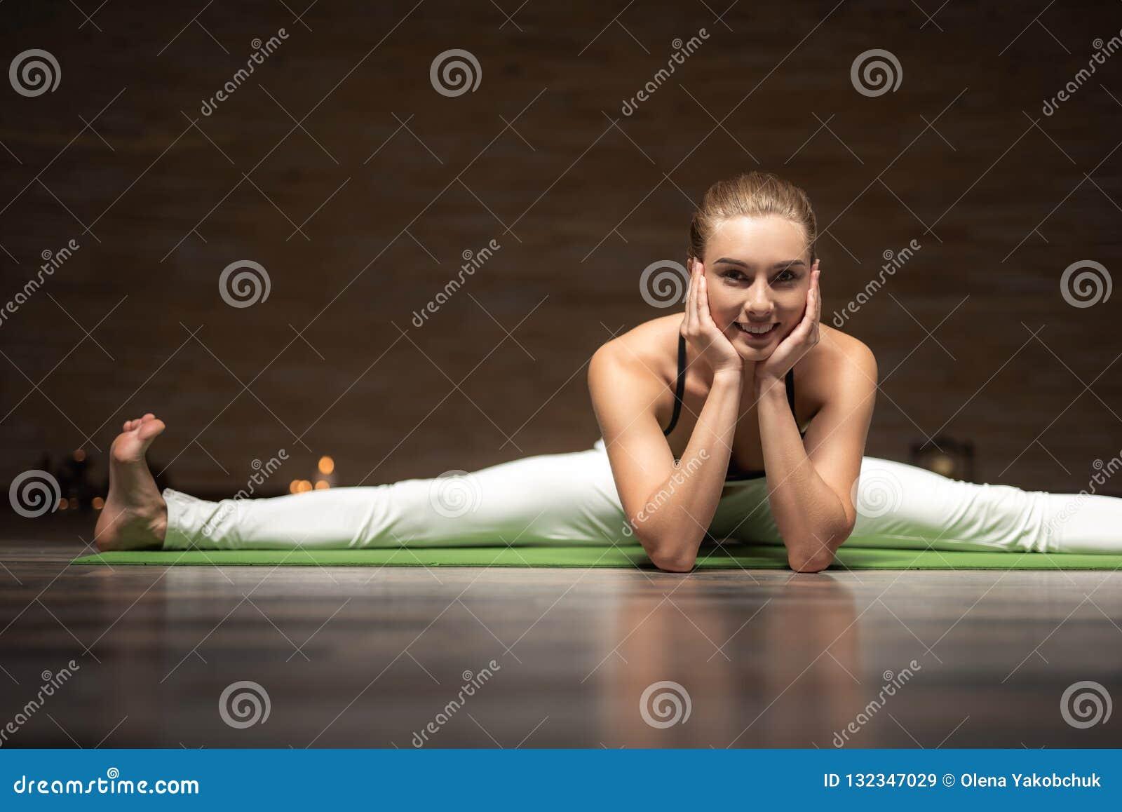 Gladlynt dam som har hennes ben att delas och sätter huvudet på hennes händer