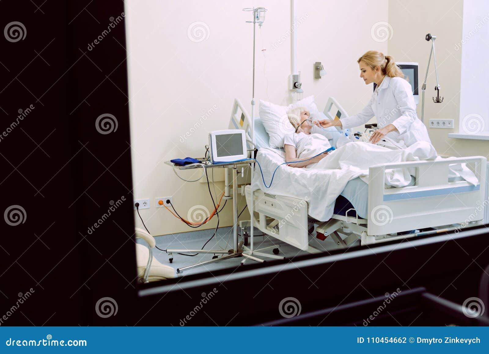 Gladlynt doktor som besöker den höga patienten med syremaskeringen