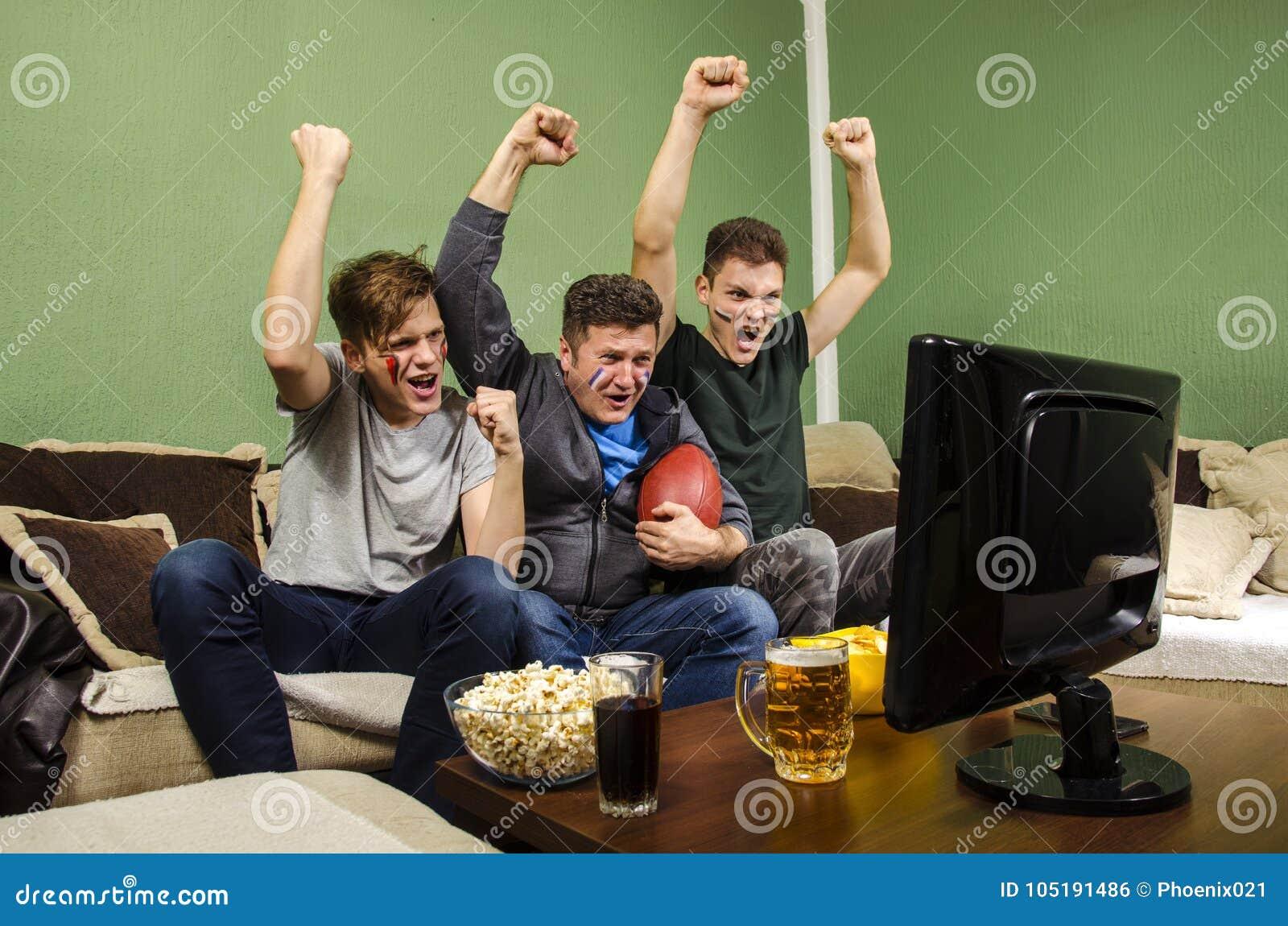 Gladlynt familj som håller ögonen på Superbowl, näve i luft