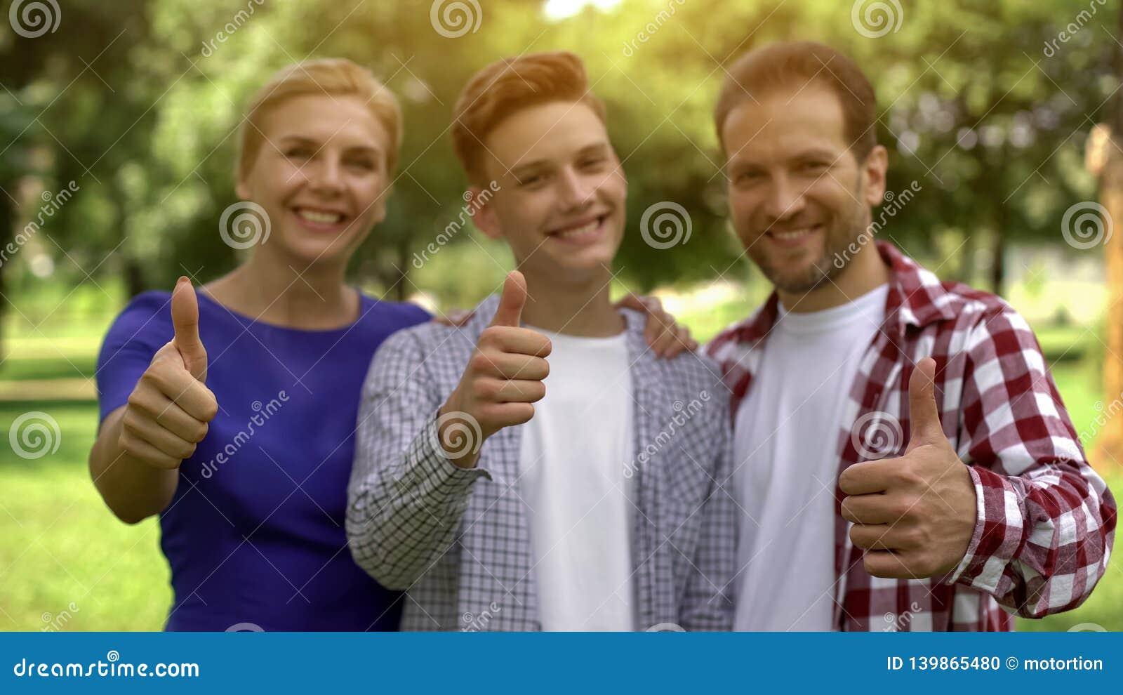 Gladlynt familj som ler visa tummar-upp, inbringande lån, krediteringar för att studera