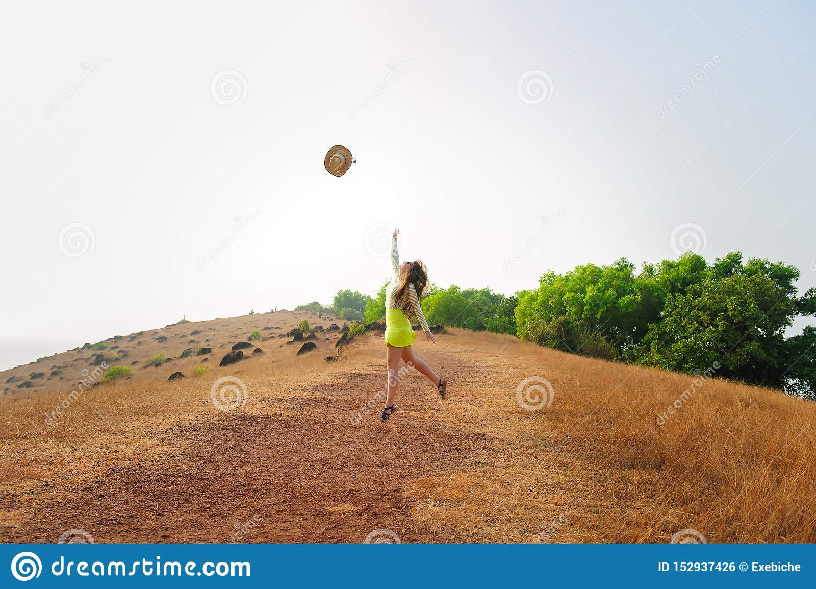 Gladlynt flicka med den långa hatten för hårhopp- och kastsugrör i luften Den unga brunettkvinnan i kort kjol går på kullen