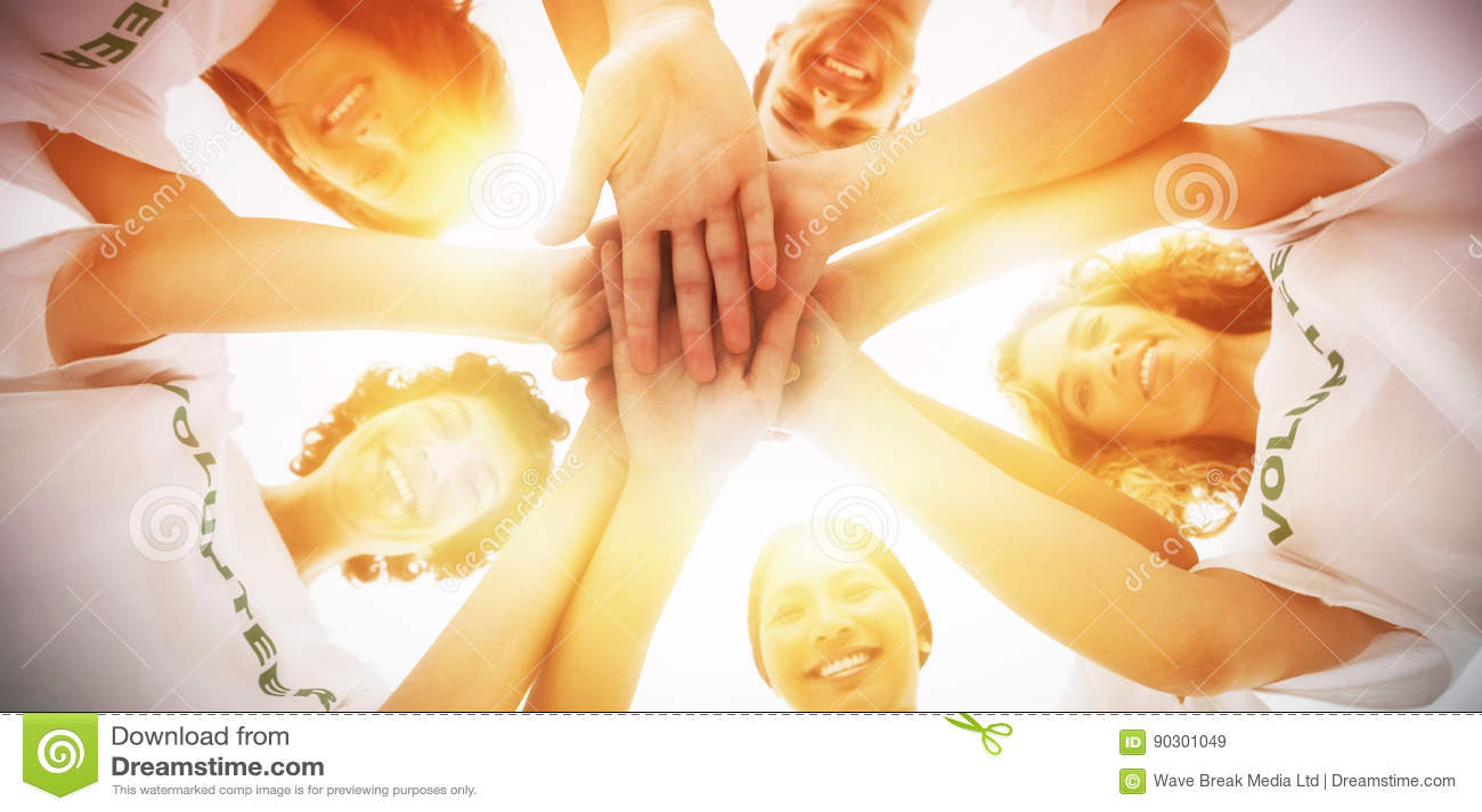 Gladlynt grupp av volontärer som tillsammans sätter händer