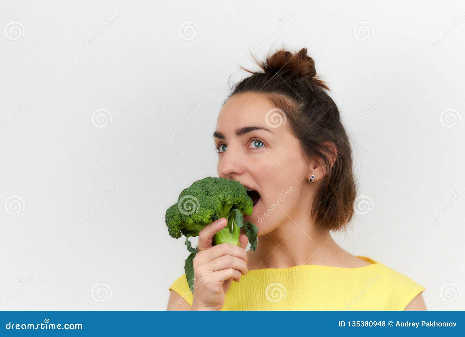 Gladlynt härligt, slankt, flicka som rymmer broccoliinflorescences i hennes händer som isoleras på en ljus bakgrund kvinna av eur
