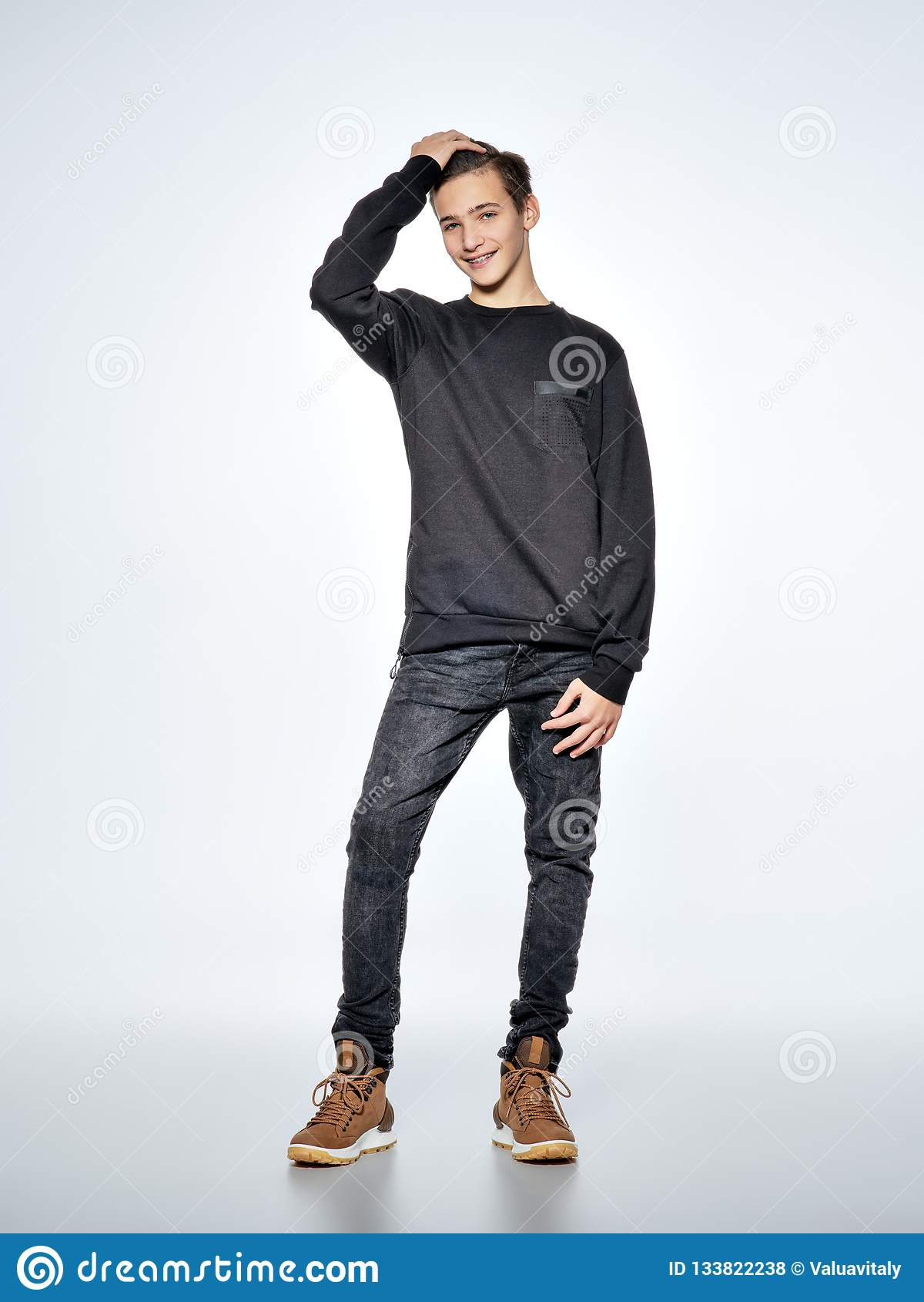 Gladlynt iklädd svart moderiktig kläder för tonårs- pojke som poserar på s