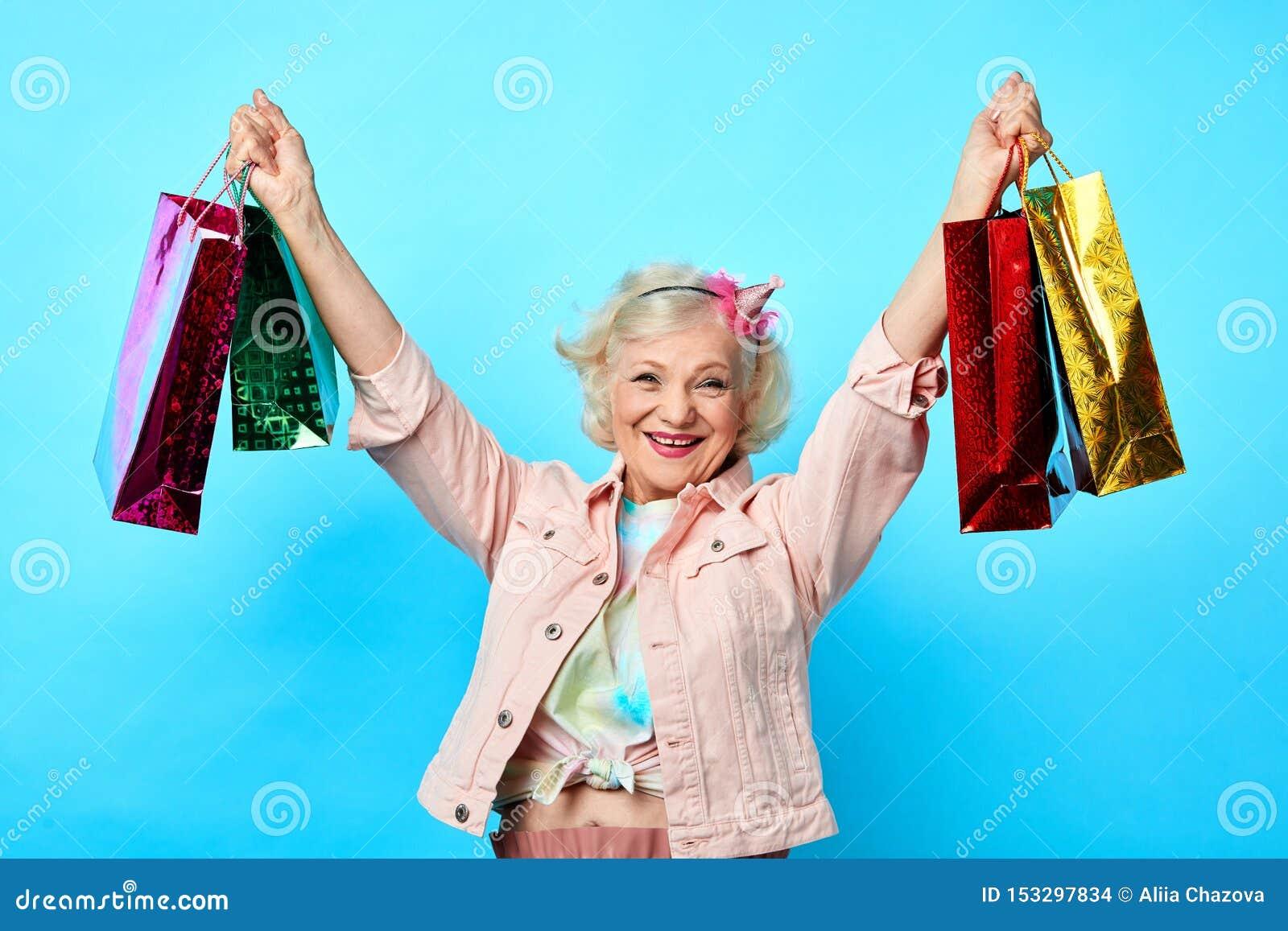 Gladlynt kall farmor med det lyftta arminnehavet många shoppa påsar