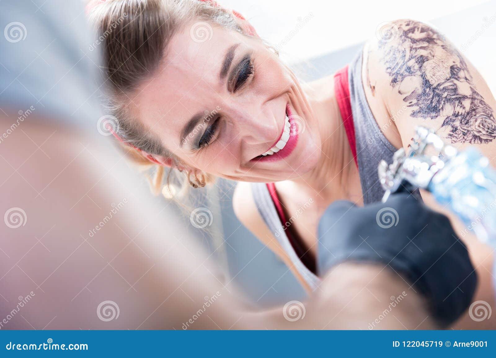 Gladlynt kvinna som ler med förtroende i en modern tatueringstudio