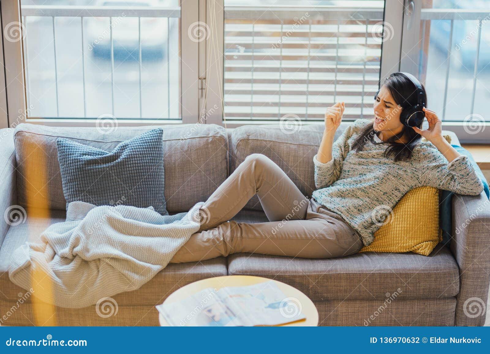 Gladlynt kvinna som lyssnar till musik med stor hörlurar och att sjunga Tycka om att lyssna till musik i fri tid hemma Koppla av