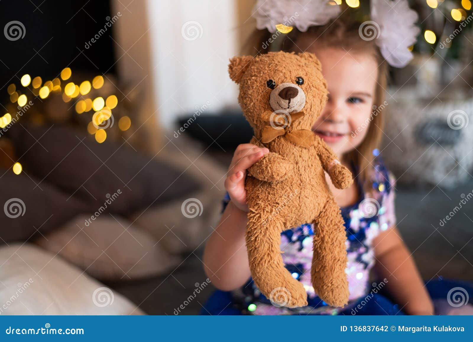 Gladlynt liten flicka som spelar med hennes fluffiga leksak