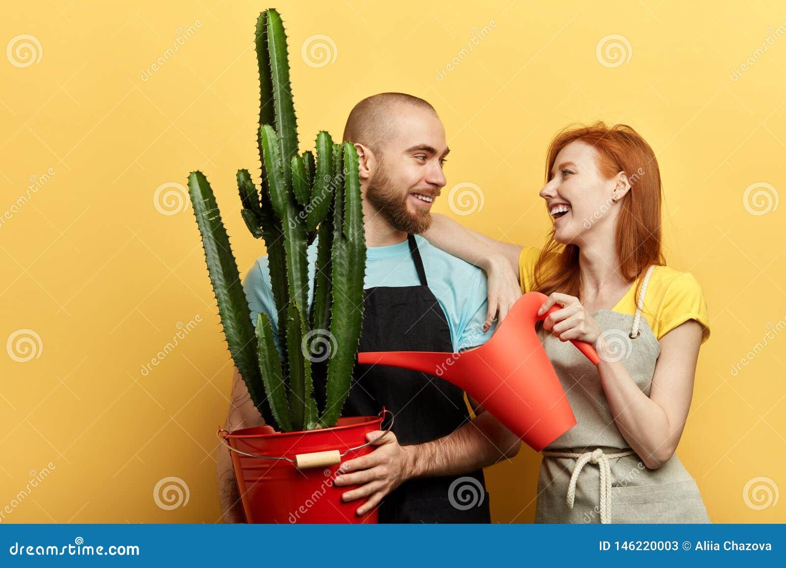 Gladlynt man och kvinna som bevattnar blommor