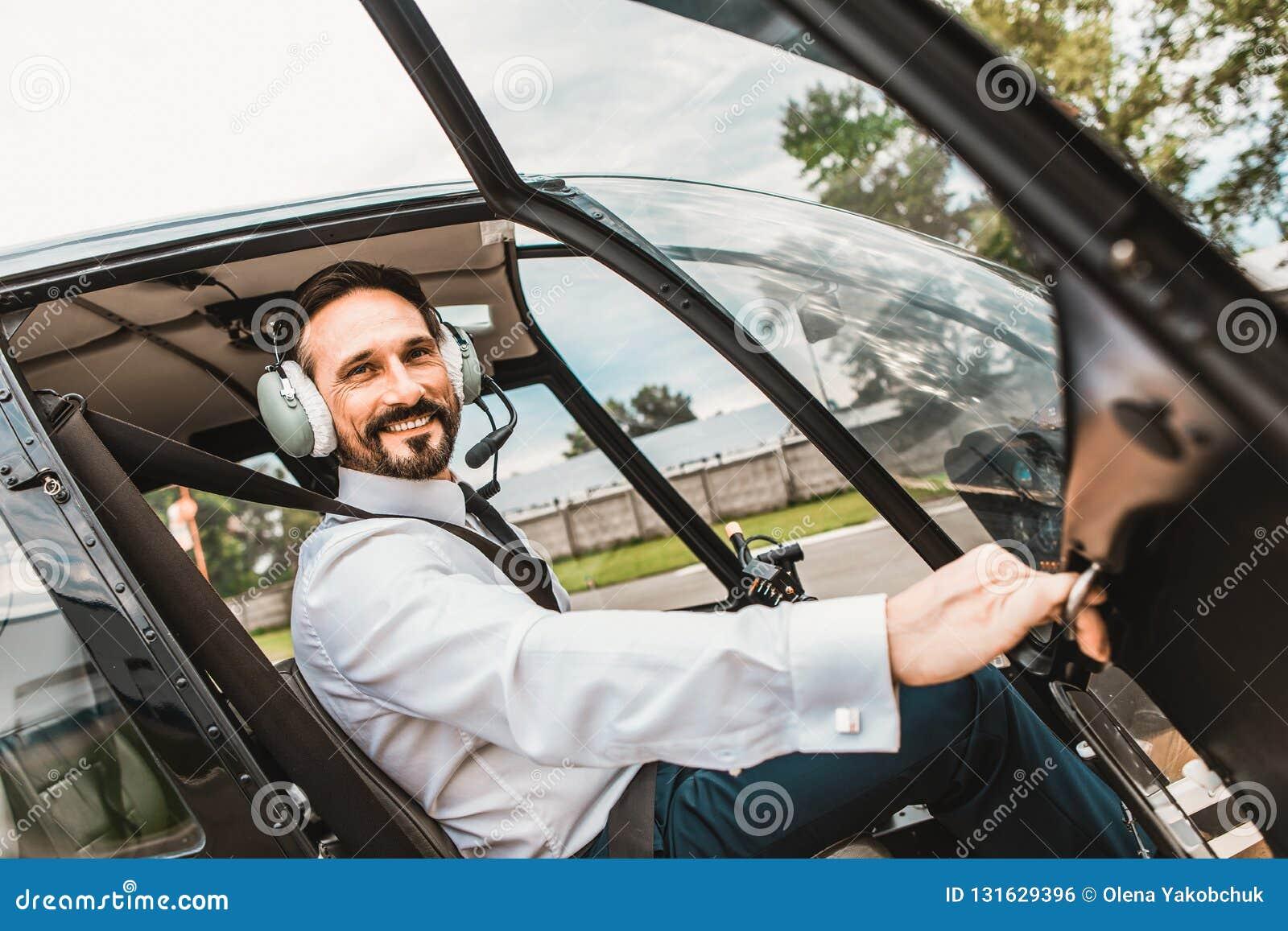 Gladlynt pilot som öppnar dörren av hans kabin och le