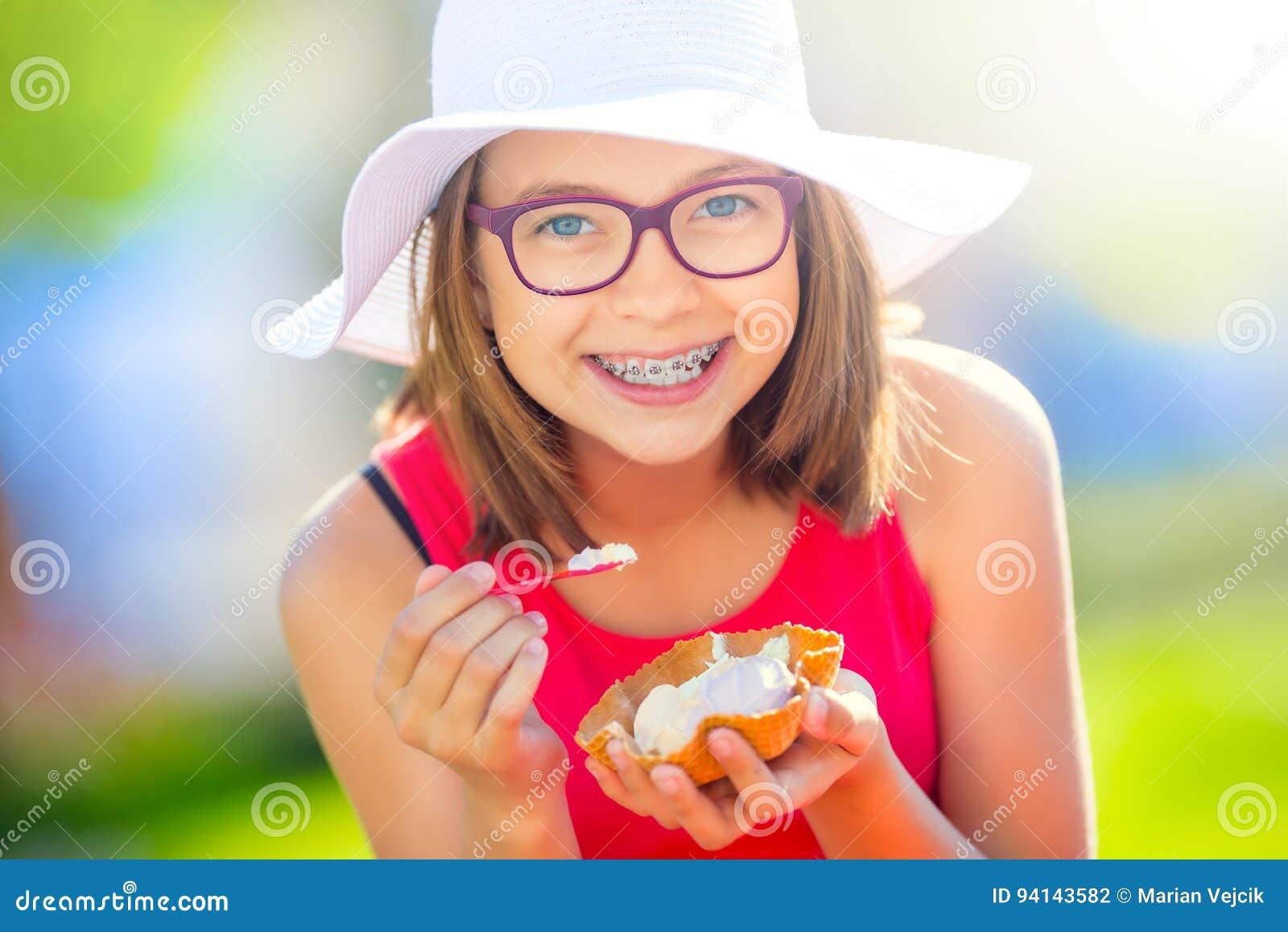 Gladlynt tonårs- flicka med tand- hänglsenexponeringsglas och glass Stående av en le nätt ung flicka i sommardräkt med is