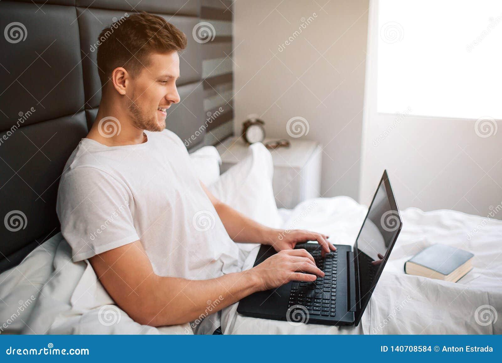 Gladlynt trevligt arbete för ung man i säng som moring tidigt Grabbhållbärbar dator och typ på tangentbordet Leende och realitet