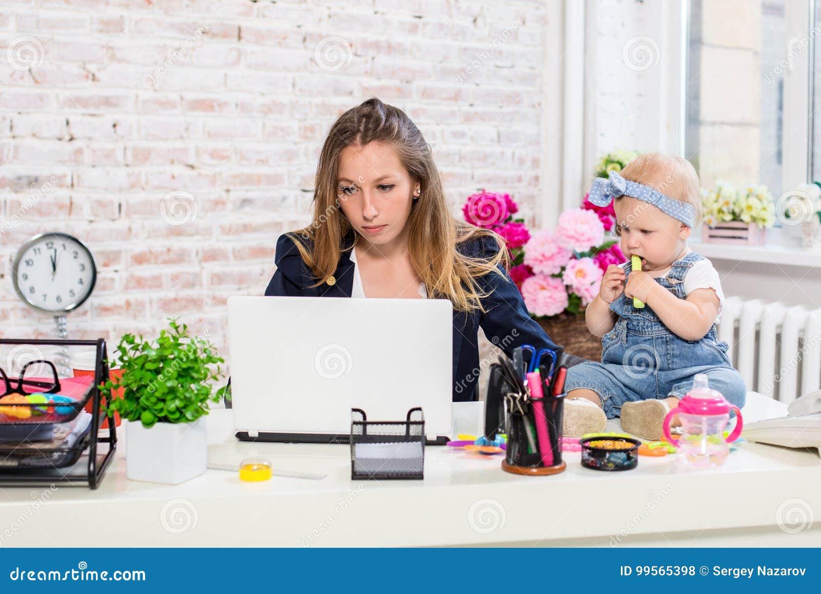 Gladlynt ung härlig affärskvinna som ser bärbara datorn, medan sitta på hennes arbetsplats med hennes lilla dotter
