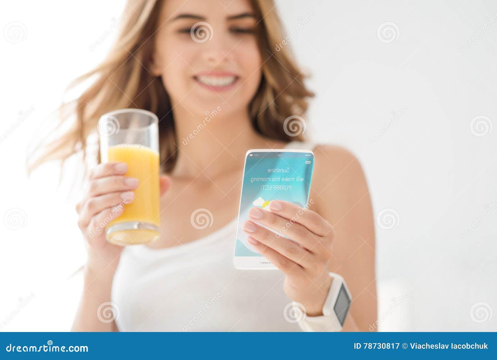 Gladlynt ung kvinna som använder mobiltelefonen
