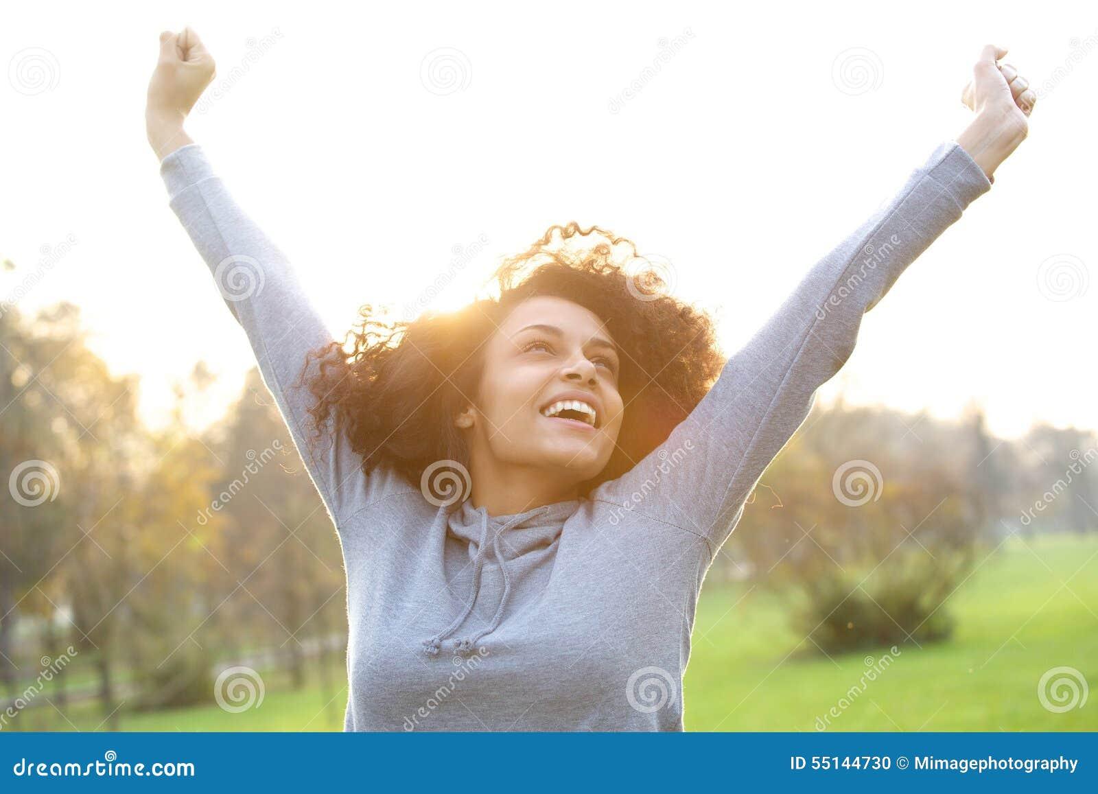 Gladlynt ung kvinna som ler med lyftta armar