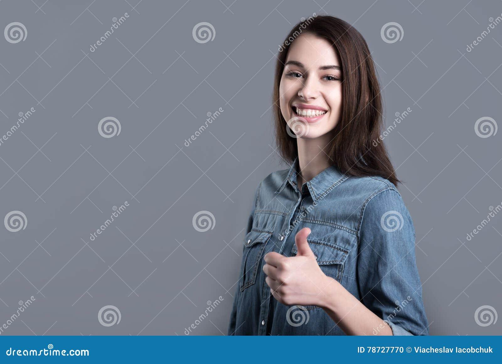 Gladlynt ung kvinna som ler och lyfter tummen