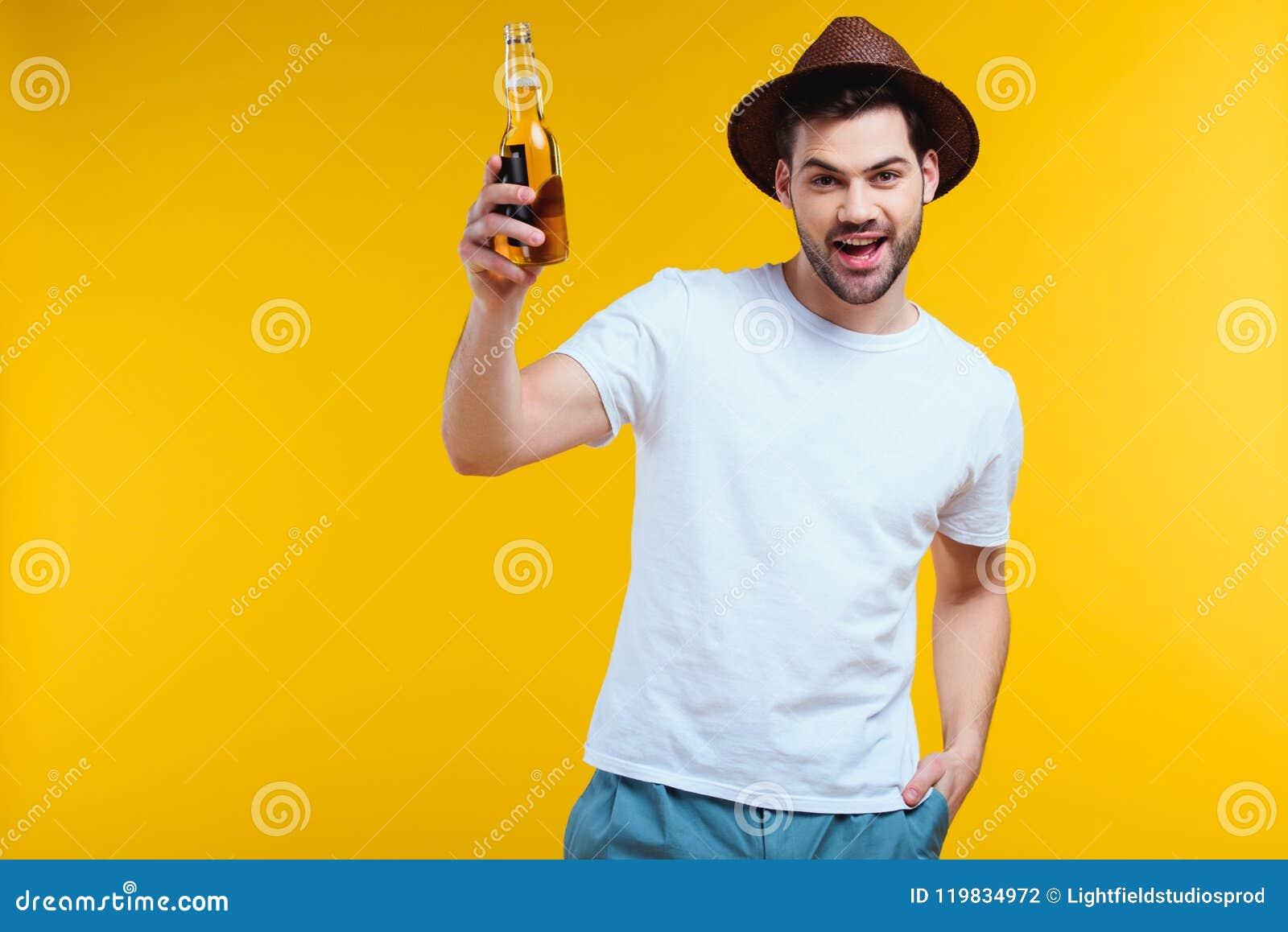 Gladlynt ung man i hållande glasflaska för hatt av drink och att le för sommar på kameran
