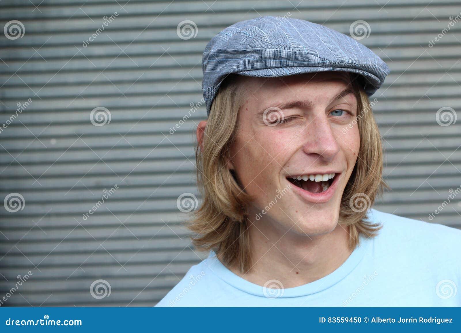 Gladlynt ung man som blinkar över grå bakgrund