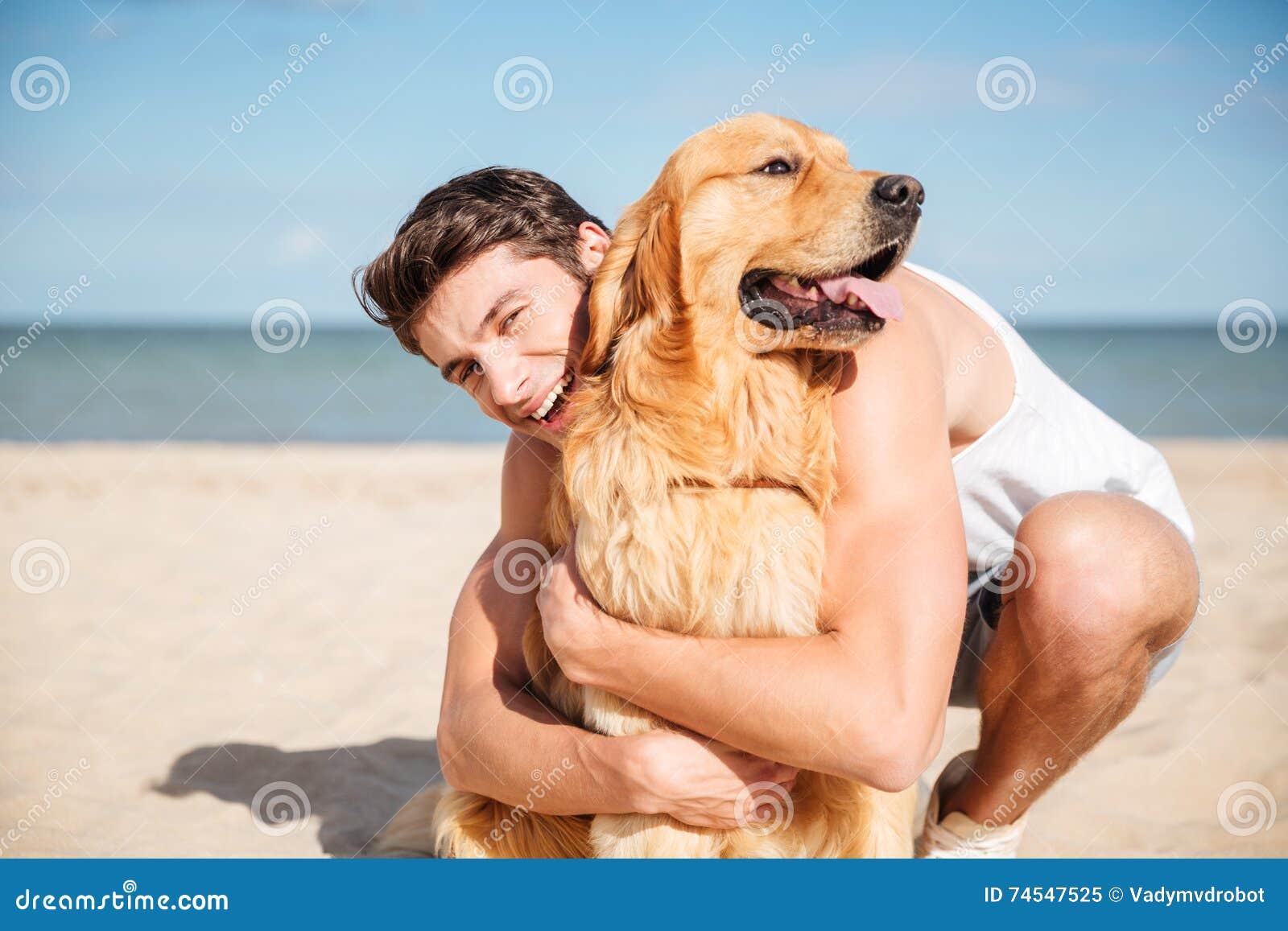 Gladlynt ung man som kramar hans hund på stranden